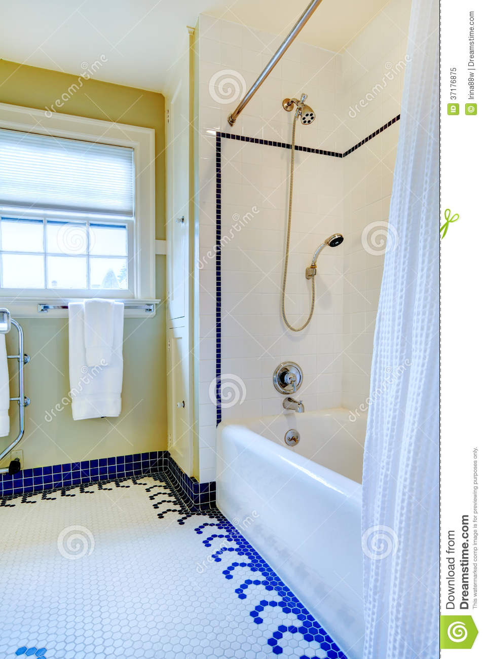 Bright Yellow And White Bathroom With Blue Tile Floor Royalty Free