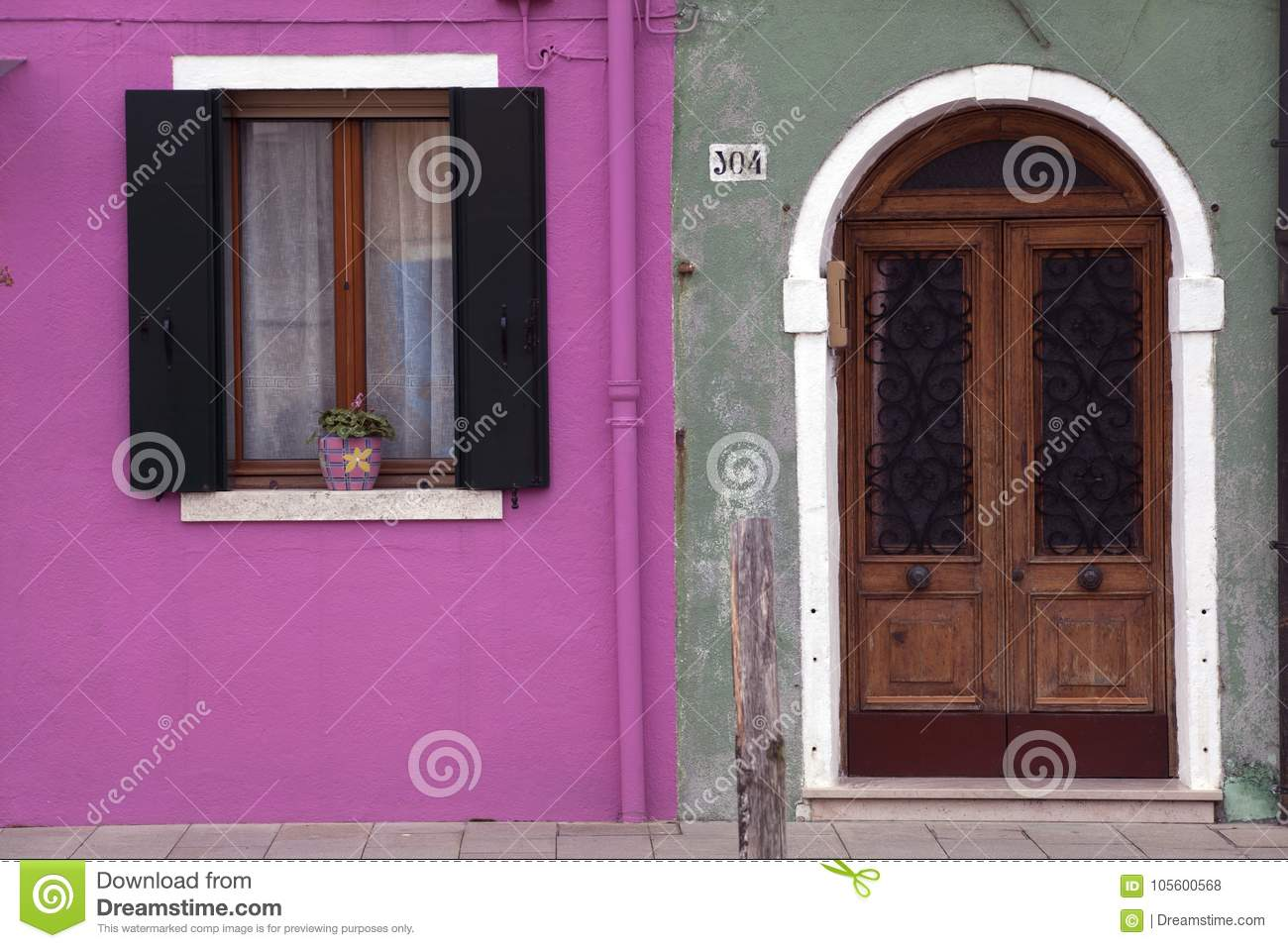 Brightly coloured pink and green house wall in Burano where houses with shutters and doors are painted in beautiful colours Burano