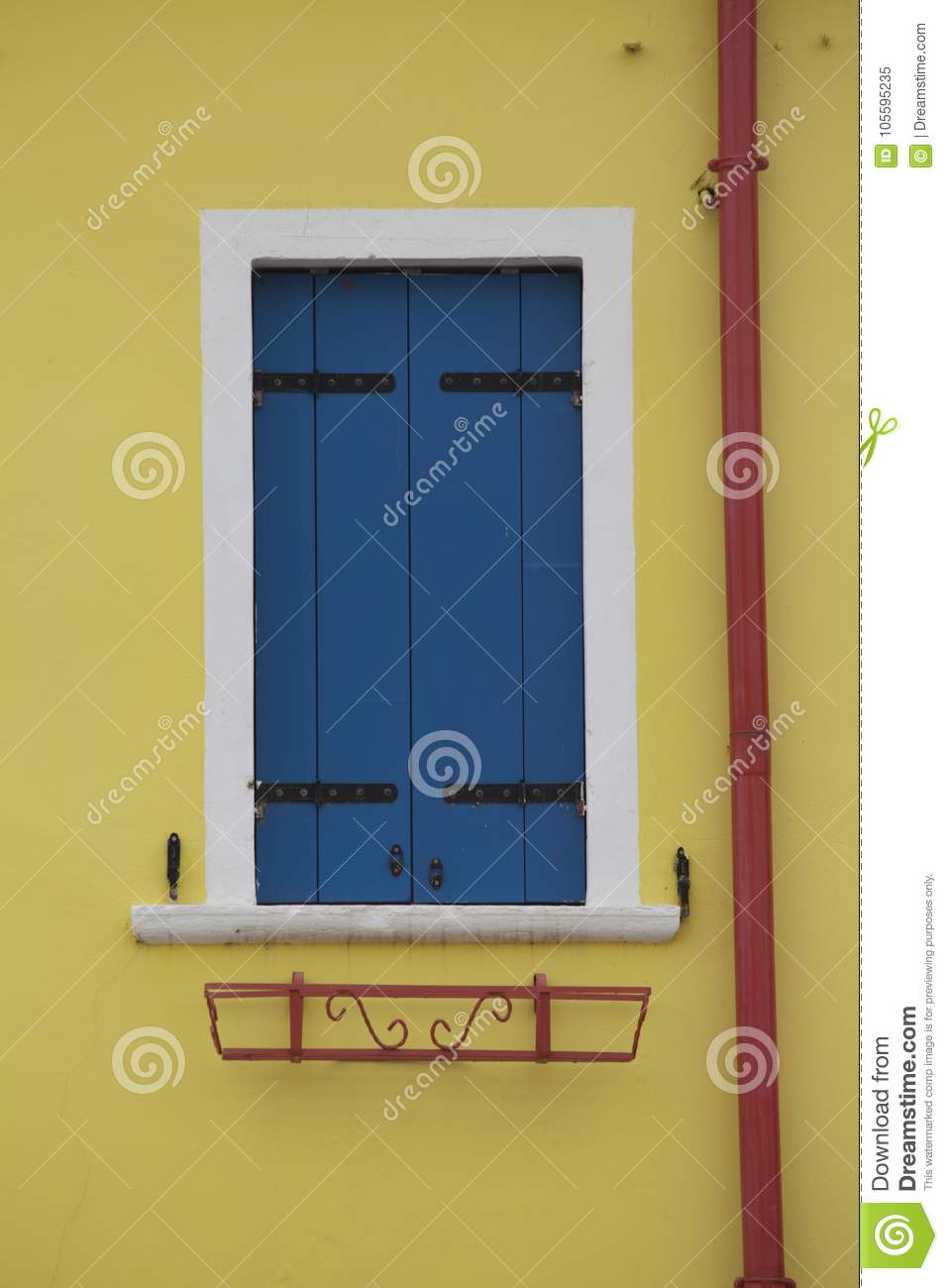 Brightly Colored Yellow Wall Blue Window Shutters And Red Drain Pipe ...