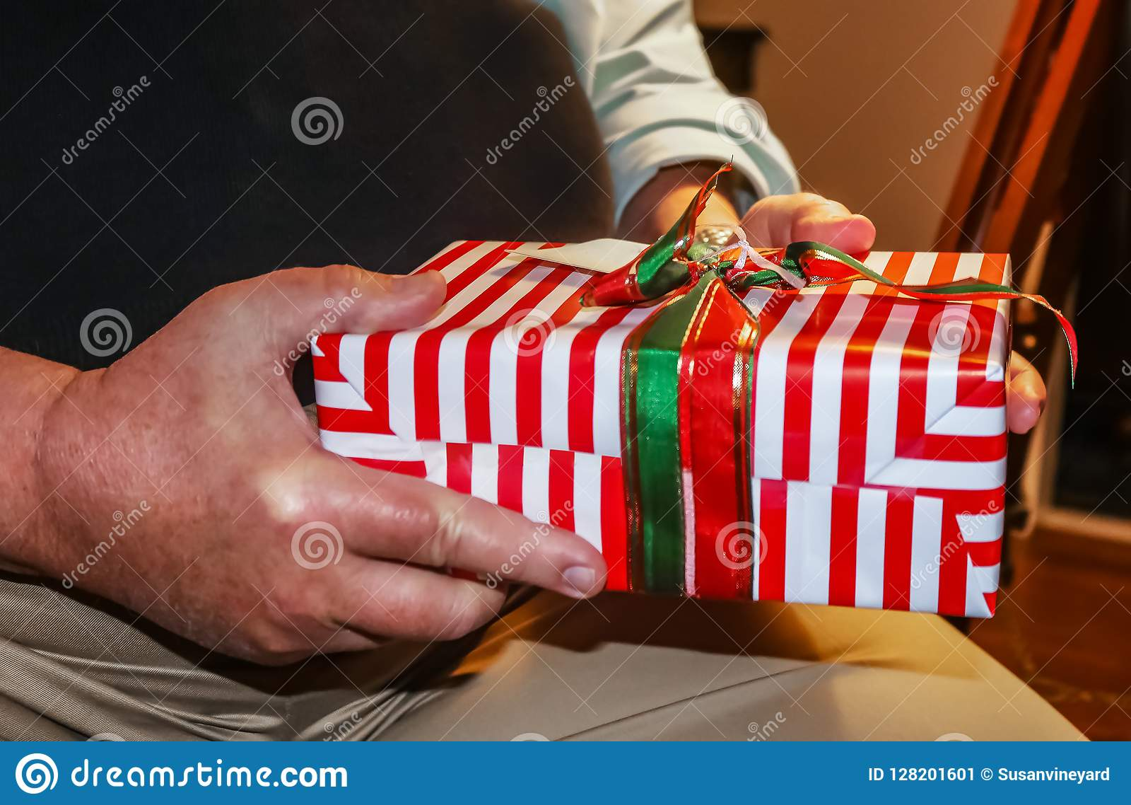 Brightly Wrapped Christmas Present In Hands Of Older Man Closeup