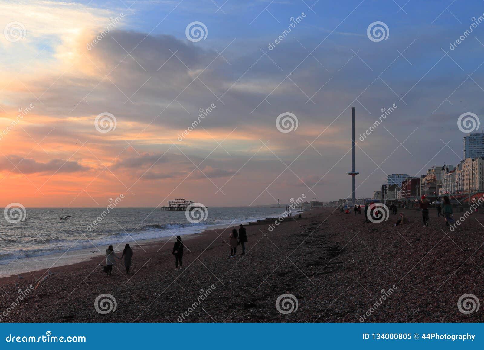 BRIGHTON, EAST SUSSEX, INGHILTERRA, REGNO UNITO - 13 NOVEMBRE 2018: La gente che gode dei colori del tramonto a Brighton Beach