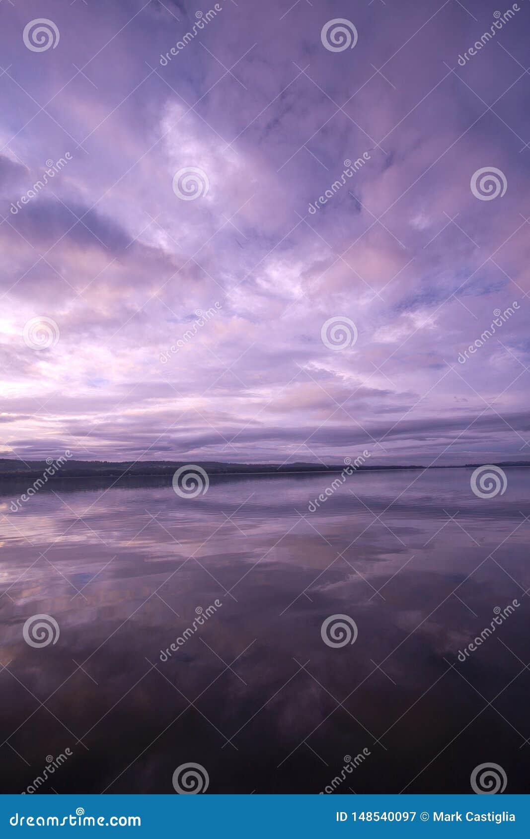 Briljante pastelkleurpinks en purples in zonsopgang over nog wateren van Meer Carmi in Franklin, VT, de V.S.