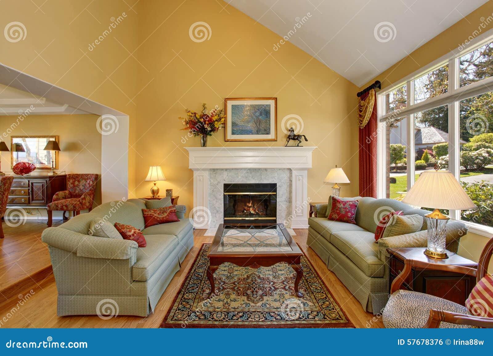Briljante woonkamer met groene banken, en gele muren stock foto ...
