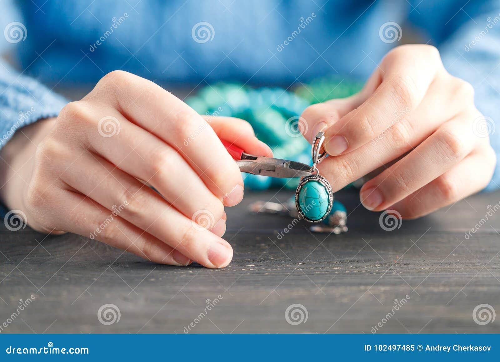 Brincos feitos a mão que fazem, oficina home O artesão da mulher cria a joia da borla Arte, passatempo, conceito do artesanato