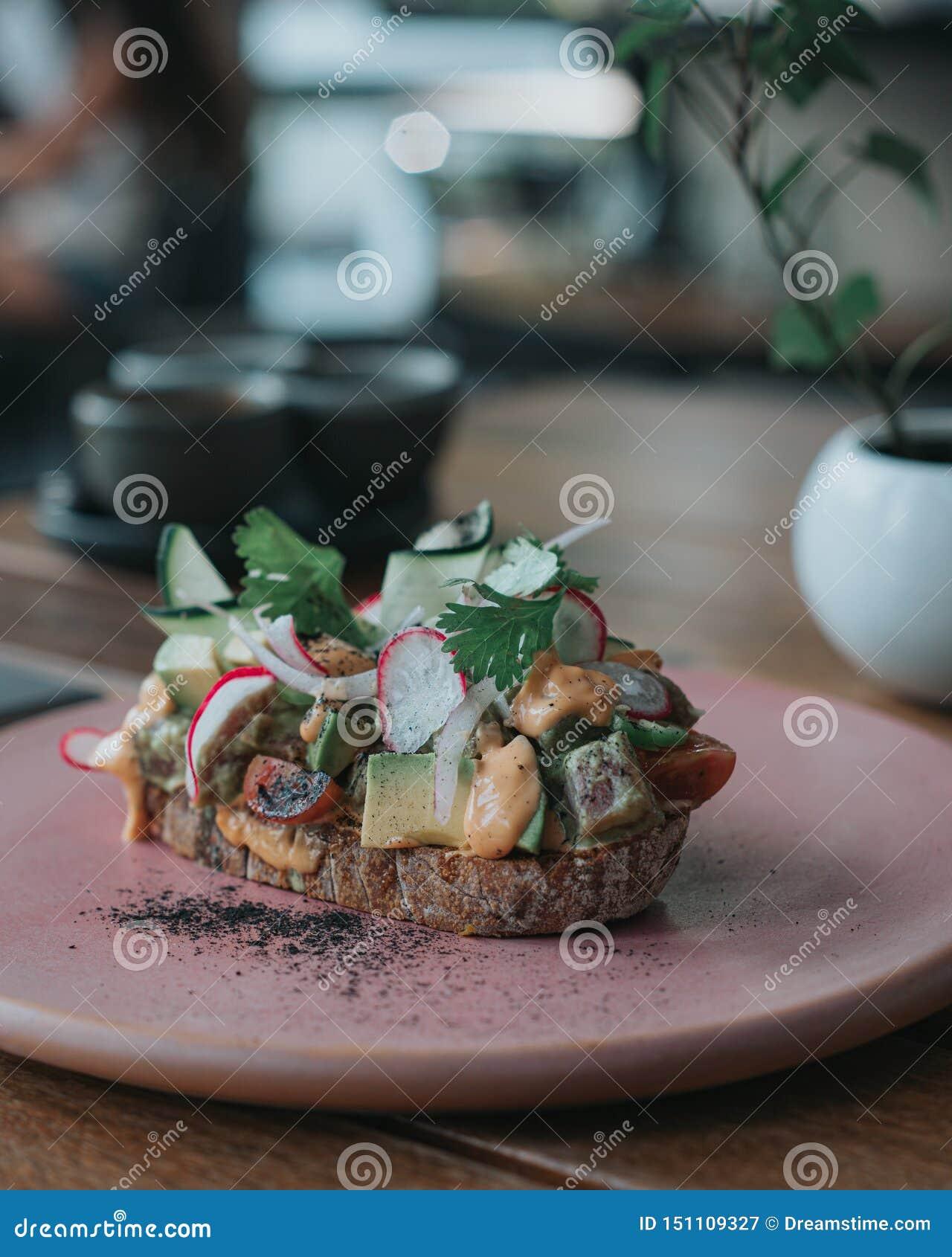 Brinde delicioso do abacate com pão artisanal em uma placa cor-de-rosa