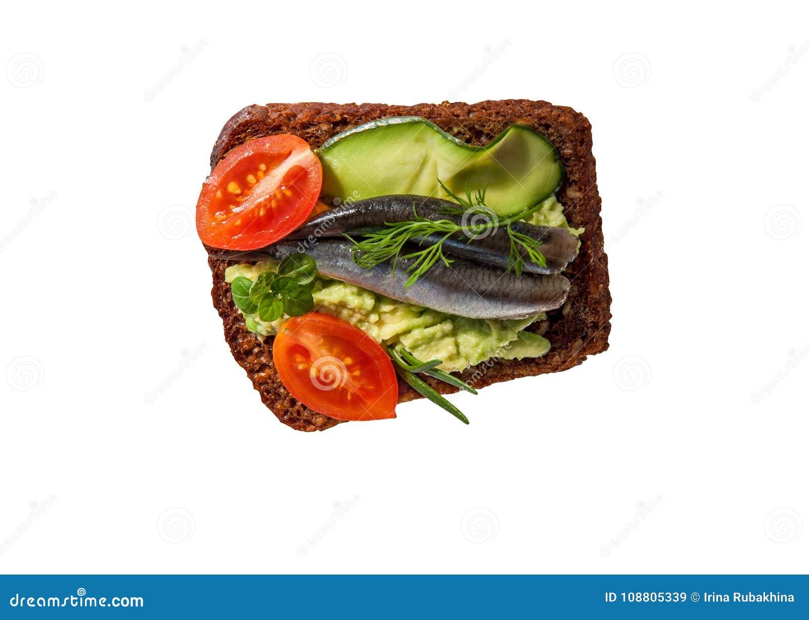 Brinde ou sanduíche no tommy marrom - pão com os tomates sem sementes do abacate, da anchova e de cereja isolados no fundo branco