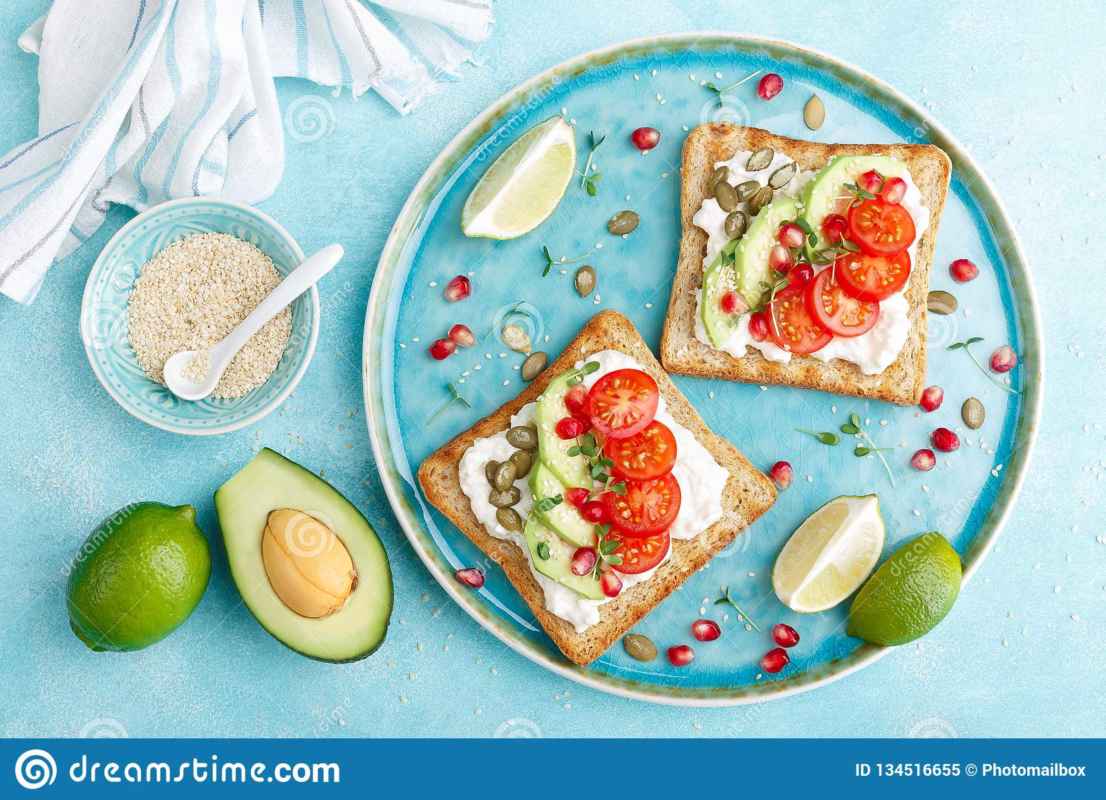 Brindes com queijo de feta, tomates, abacate, romã, sementes de abóbora e brotos do flaxseed Café da manhã da dieta delicioso e s