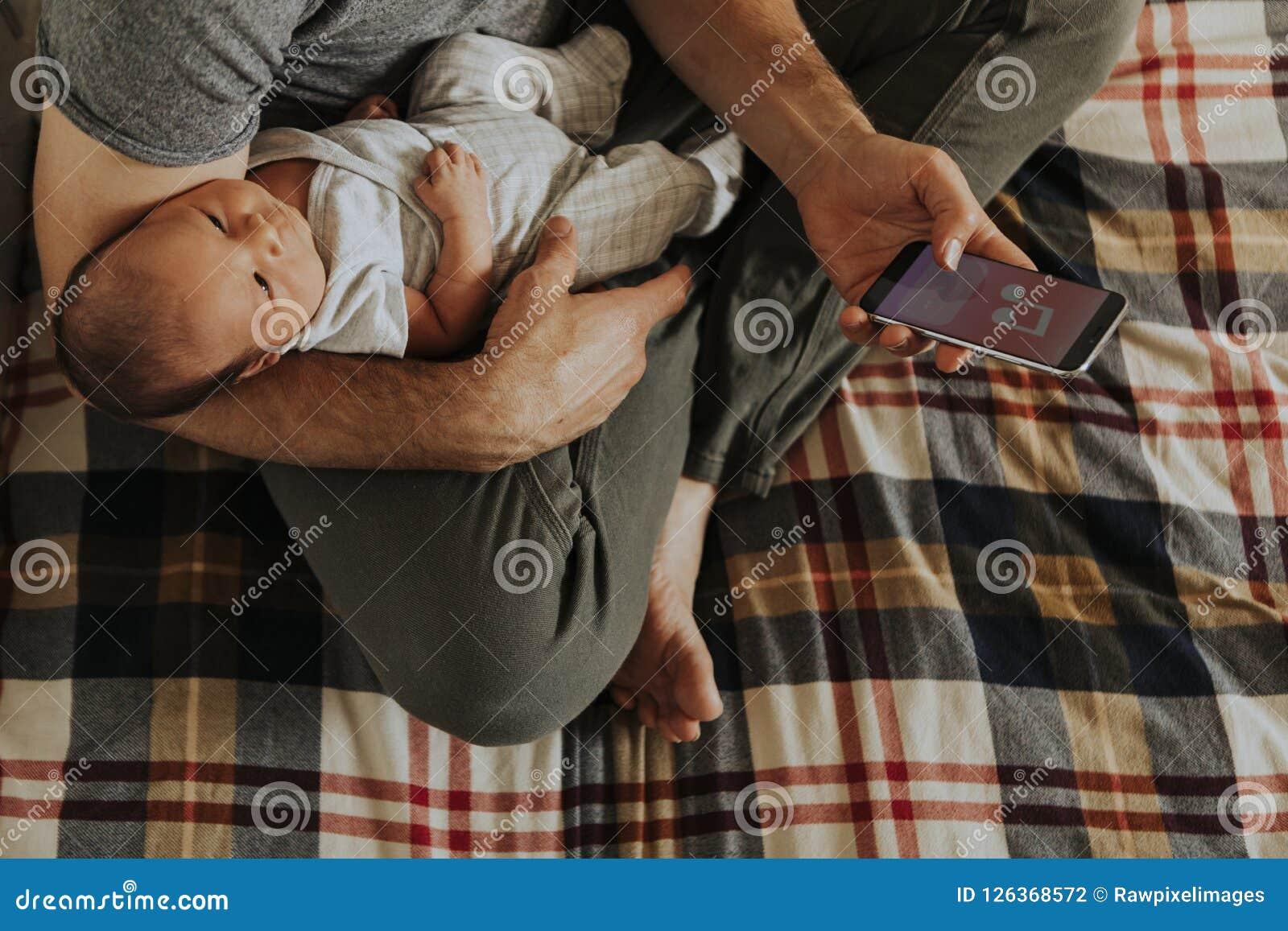 Bringen Sie das Halten seines Babys bei der Anwendung seines Telefons hervor