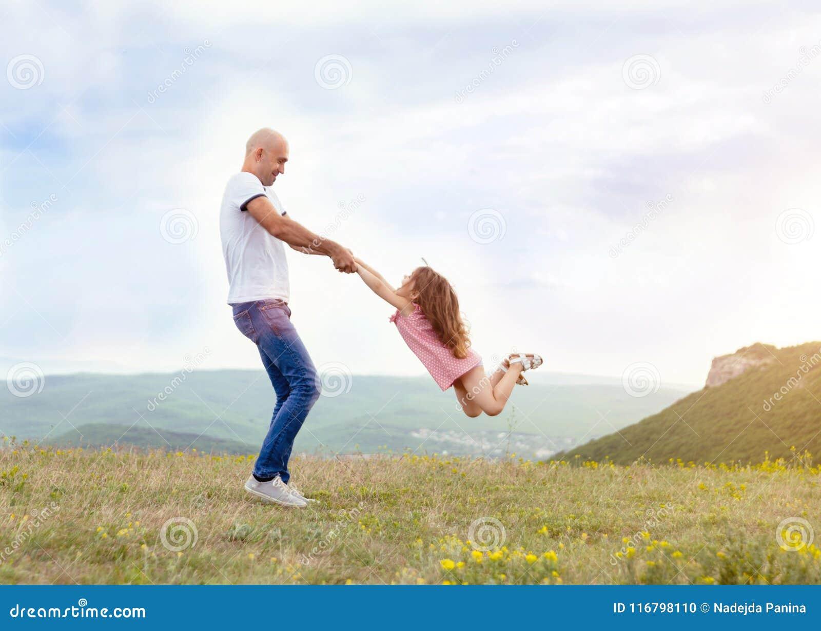 Bringen Sie das Spielen mit seiner Tochter auf dem sonnigen Gebiet hervor