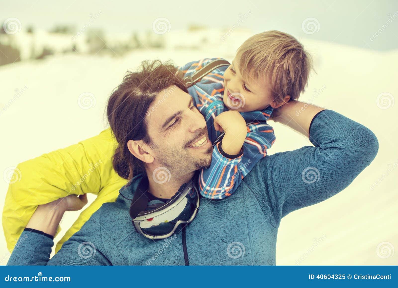 Bringen Sie seinen Sohn in den Schnee mit Weichheit liebevoll anheben hervor