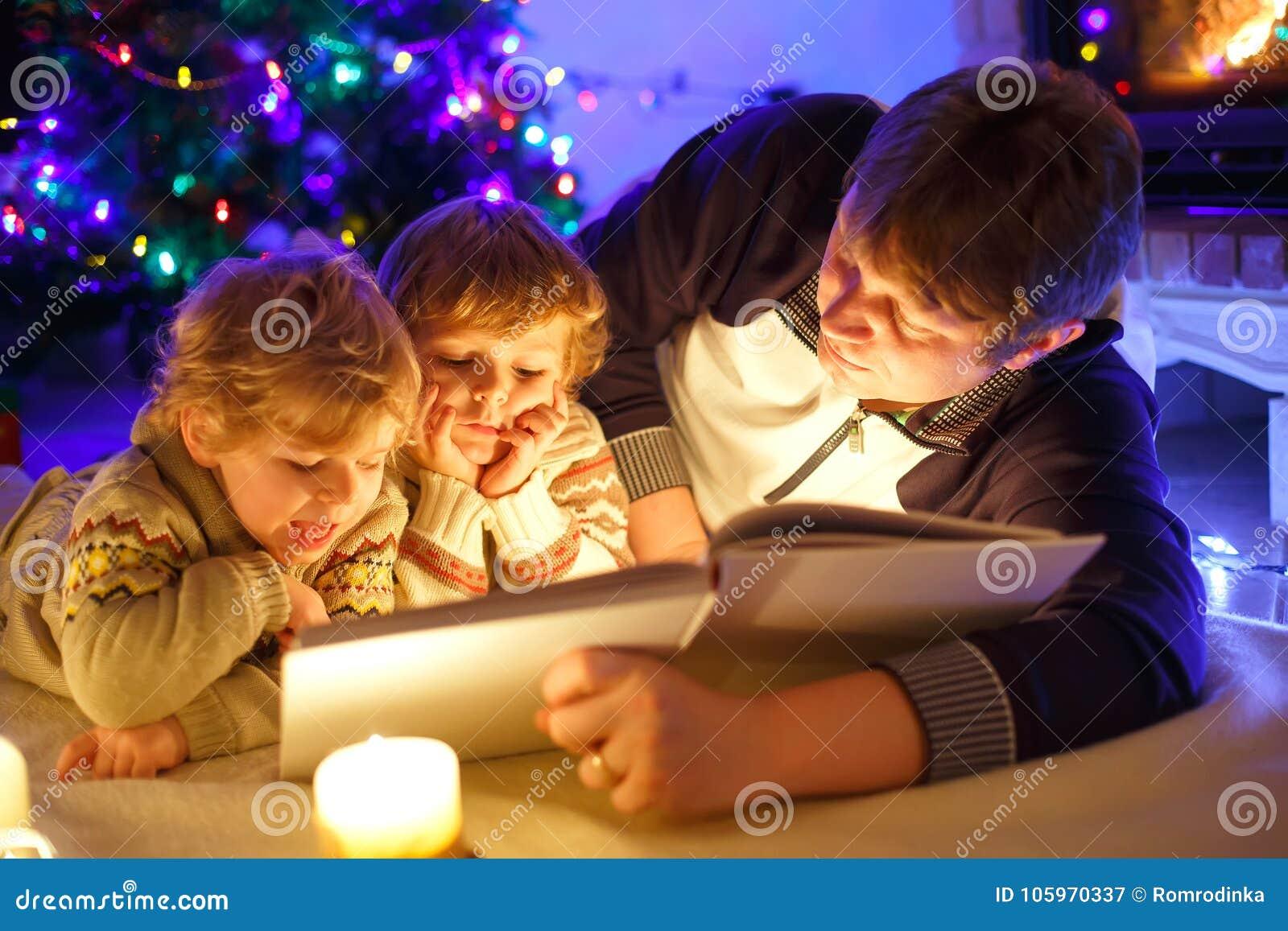 bringen sie und buch mit zwei kleines kleinkindjungen lesedurch kamin kerzen und kamin hervor. Black Bedroom Furniture Sets. Home Design Ideas