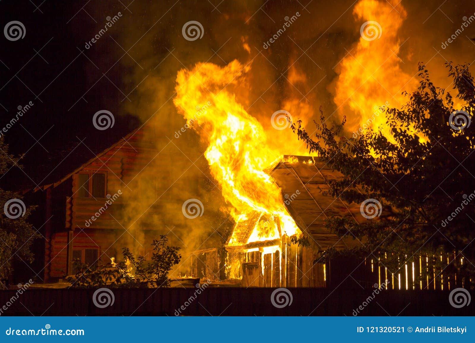 Brinnande trähus på natten Ljusa apelsinflammor och tät rök från under det belade med tegel taket på mörkt himmel, trädkonturer o