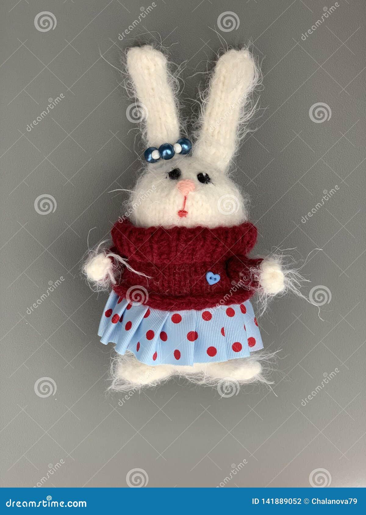Brinquedo feito malha feito a mão Coelhinho da Páscoa na camiseta vermelha com e na saia azul Brinquedo do Natal do coelho hare