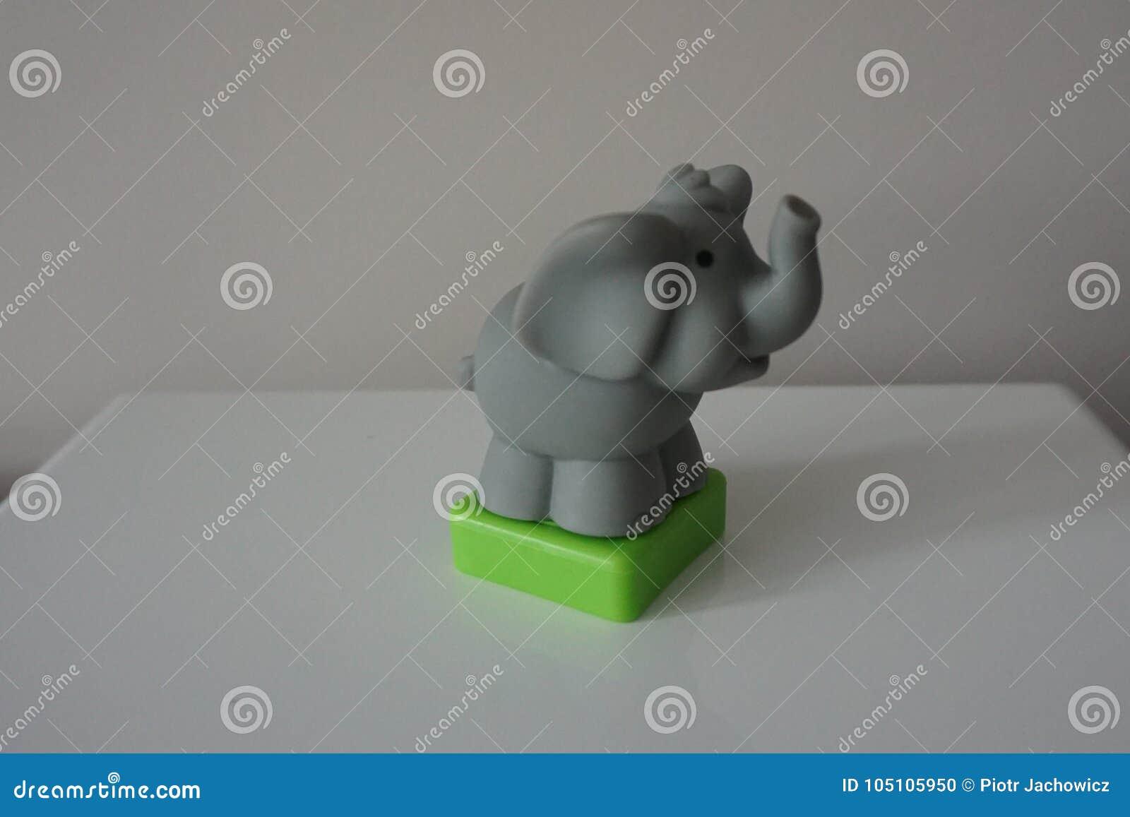 Brinquedo plástico do elefante cinzento no fundo branco