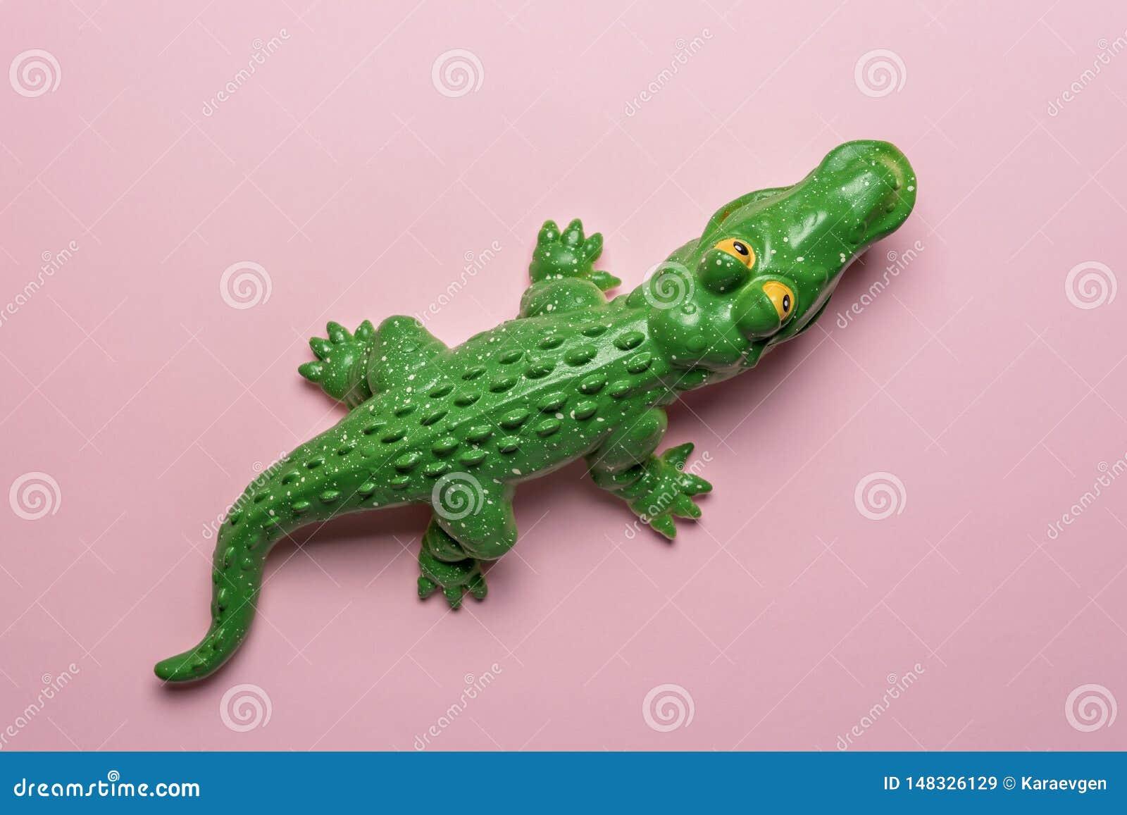 Brinquedo verde do crocodilo no fundo cor-de-rosa pastel Art Concept m?nimo