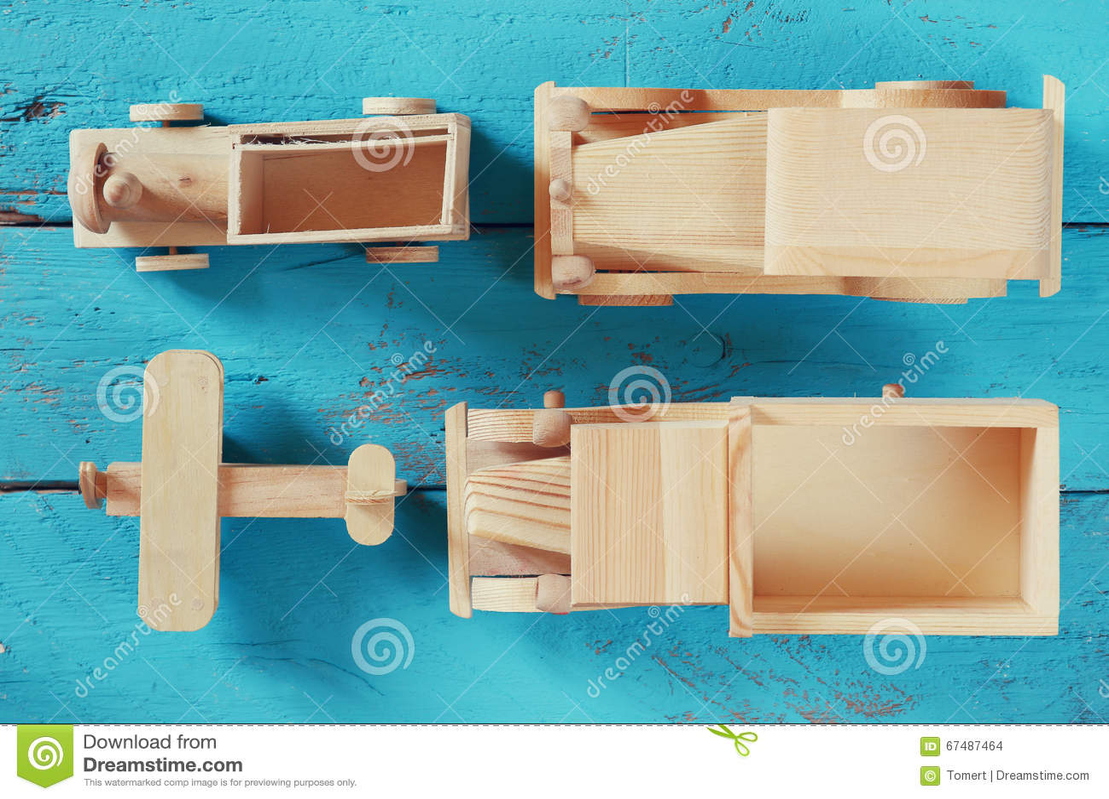 Brinquedos de madeira velhos do transporte: trem, carro, trilha e plano no fundo de madeira azul vintage filtrado e tonificado