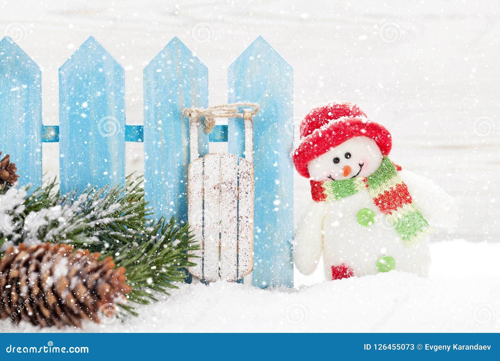 Brinquedos do boneco de neve e do pequeno trenó do Natal e ramo de árvore do abeto