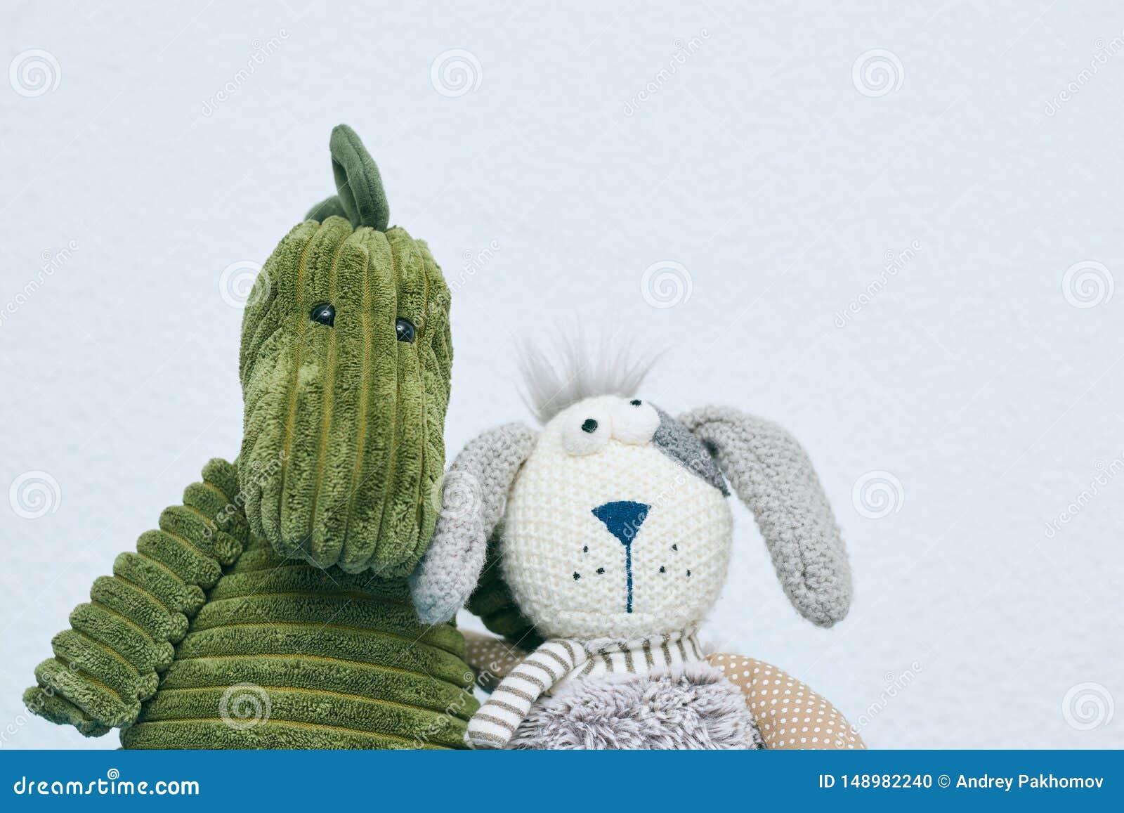 Brinquedos do luxuoso do coelho cinzento e do dinossauro verde para crian?as em um fundo claro Vista horizontal Copie o espa?o o