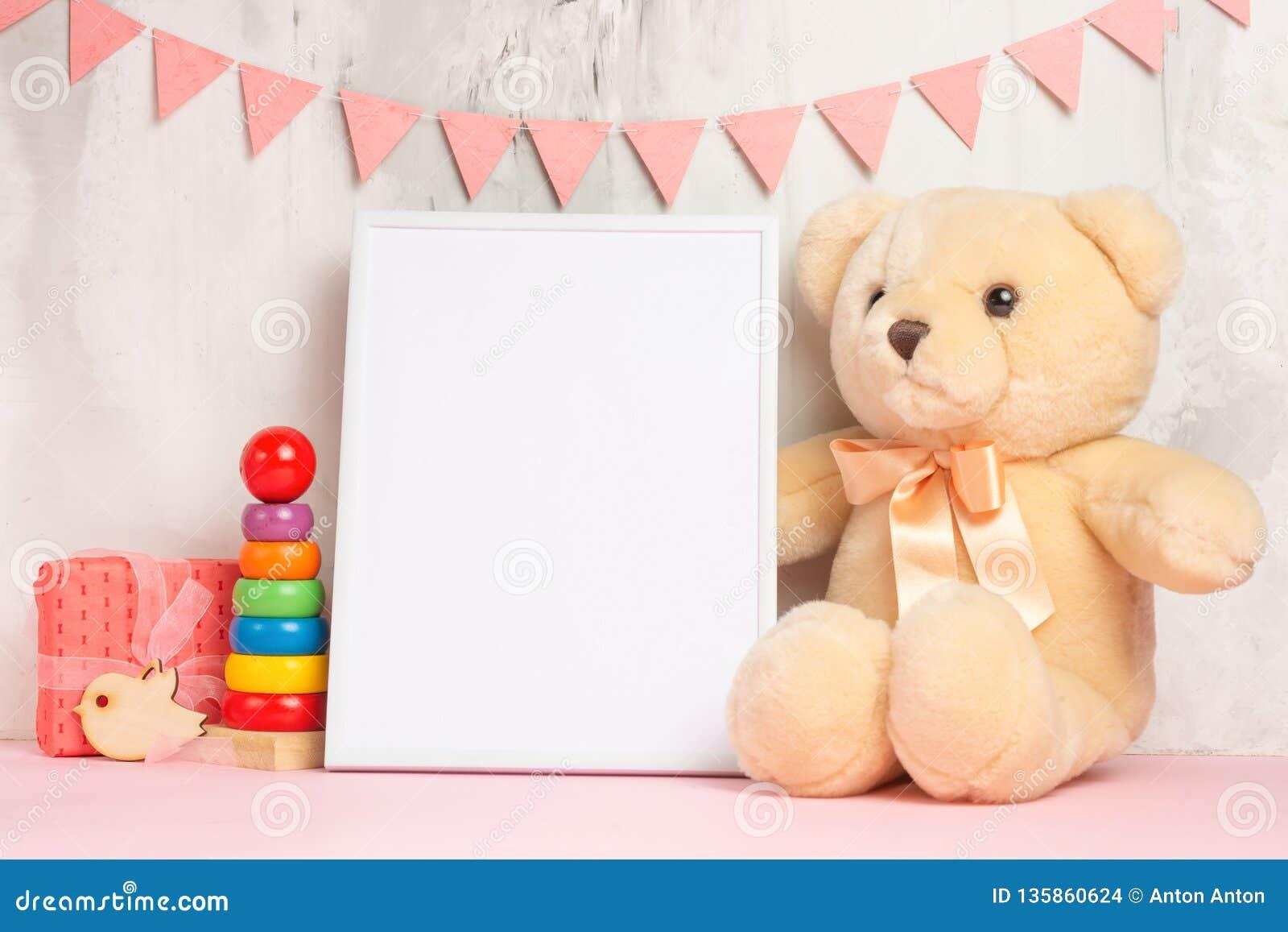 Brinquedos e quadro do bebê no fundo claro da parede, para o projeto Chuveiro de bebê