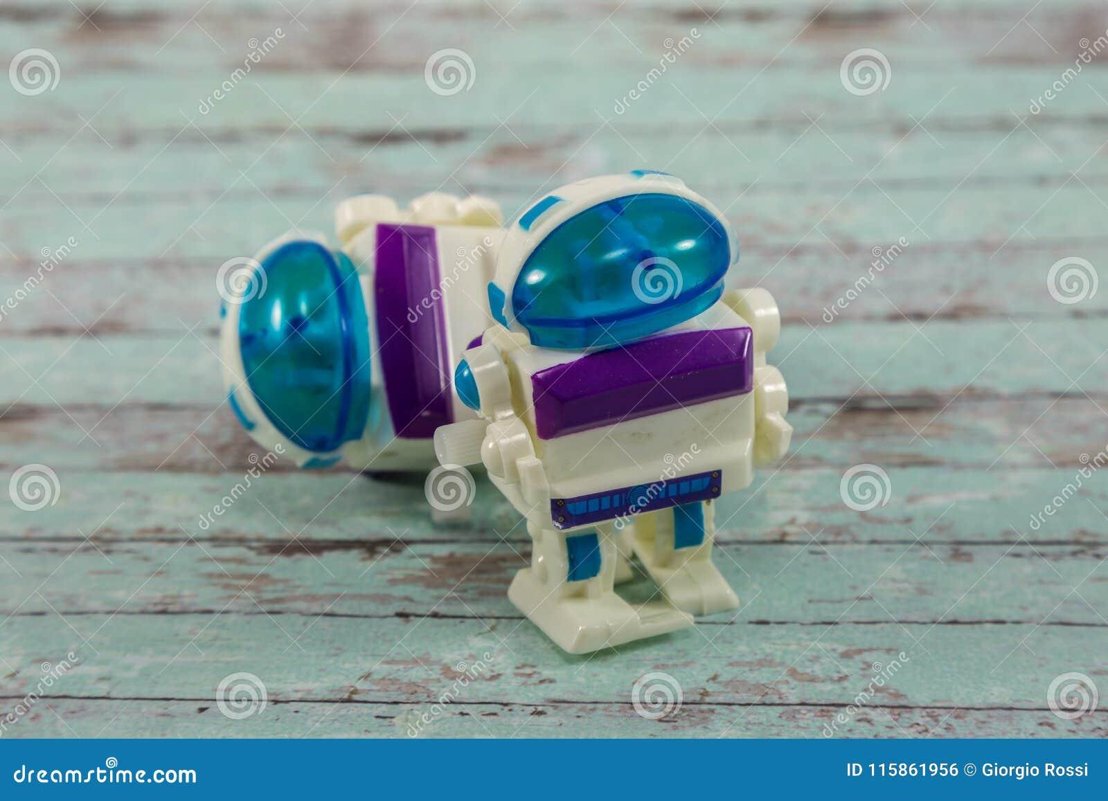 Brinquedos plásticos pequenos do robô na tabela de madeira branca