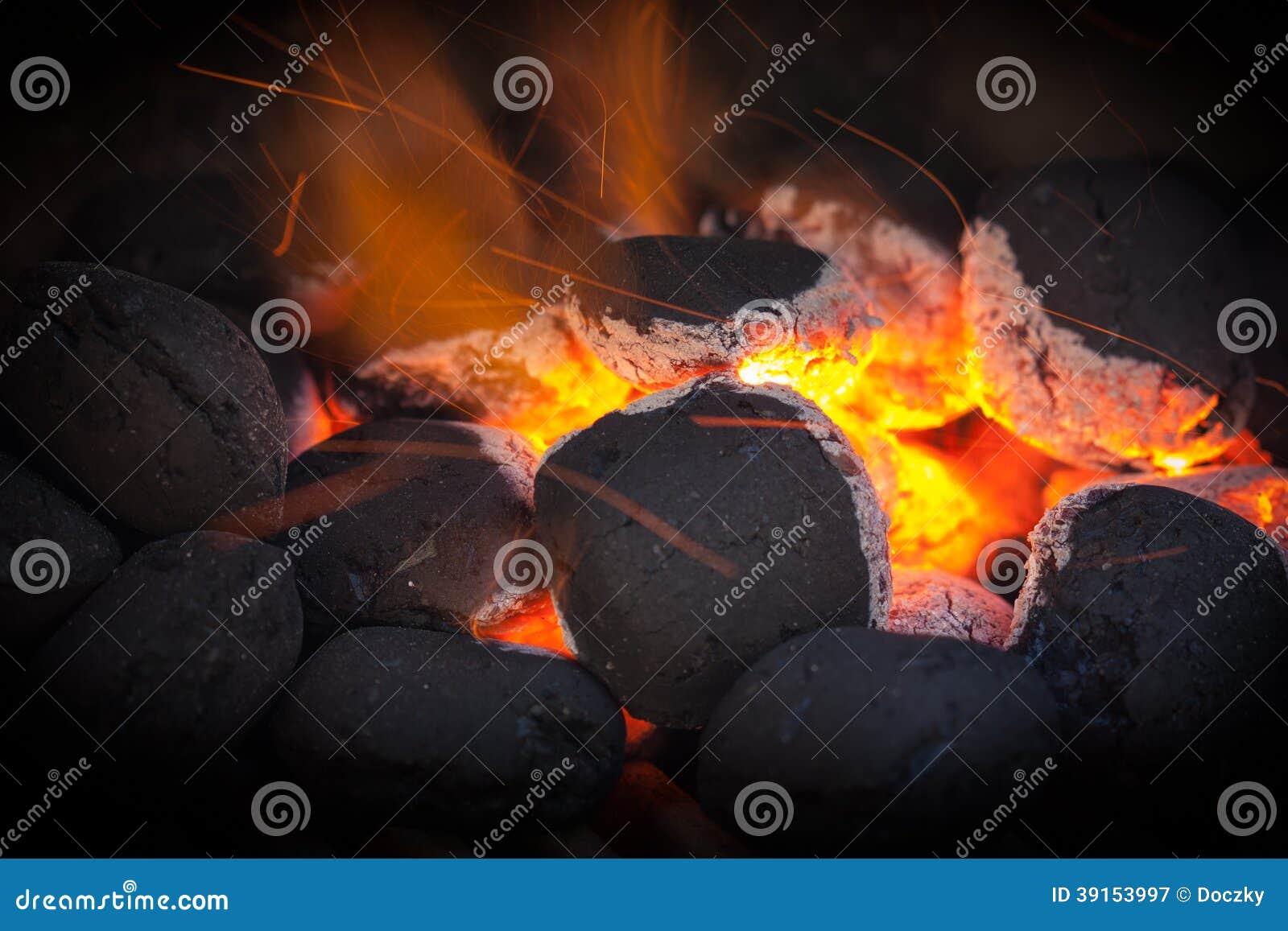 Briquetas del carbón de leña con las chispas del fuego.