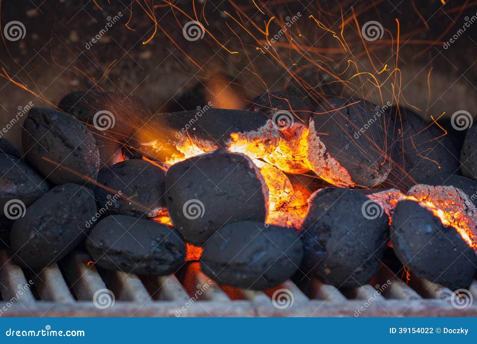 Briquettes de charbon de bois avec des étincelles du feu.