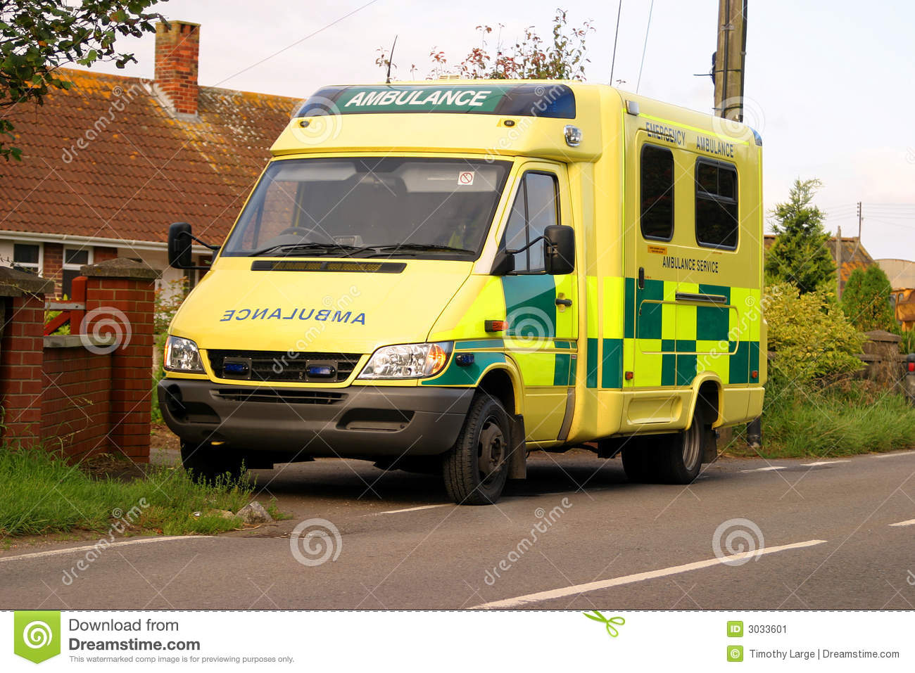 Bright yellow British Ambulance parked beside the road.
