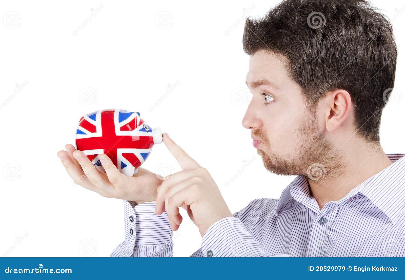 British man playing with piggy bank