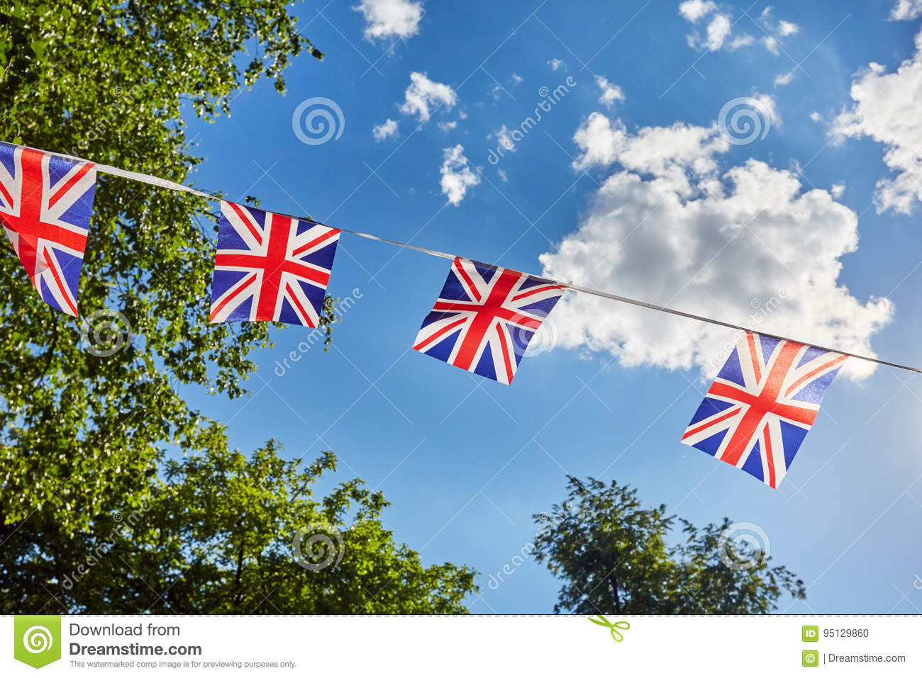 British Union Jack bunting flags against sky and green trees