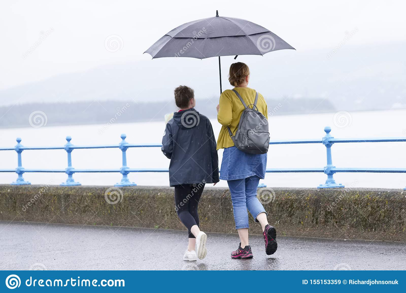 British wet summer umbrella weather with mother and daughter