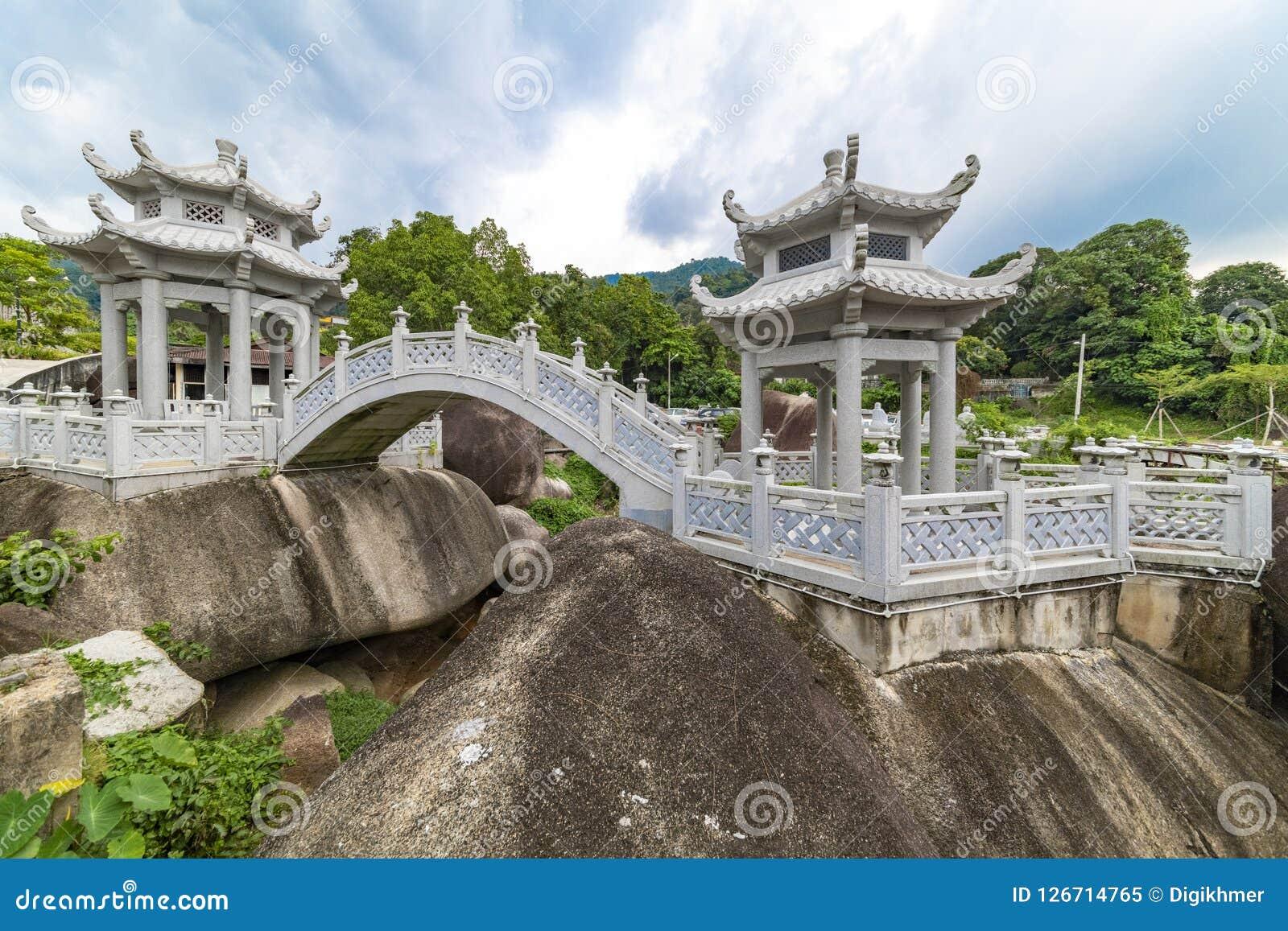 Bro och trädgård av den Kek Lok Si Buddhist templet