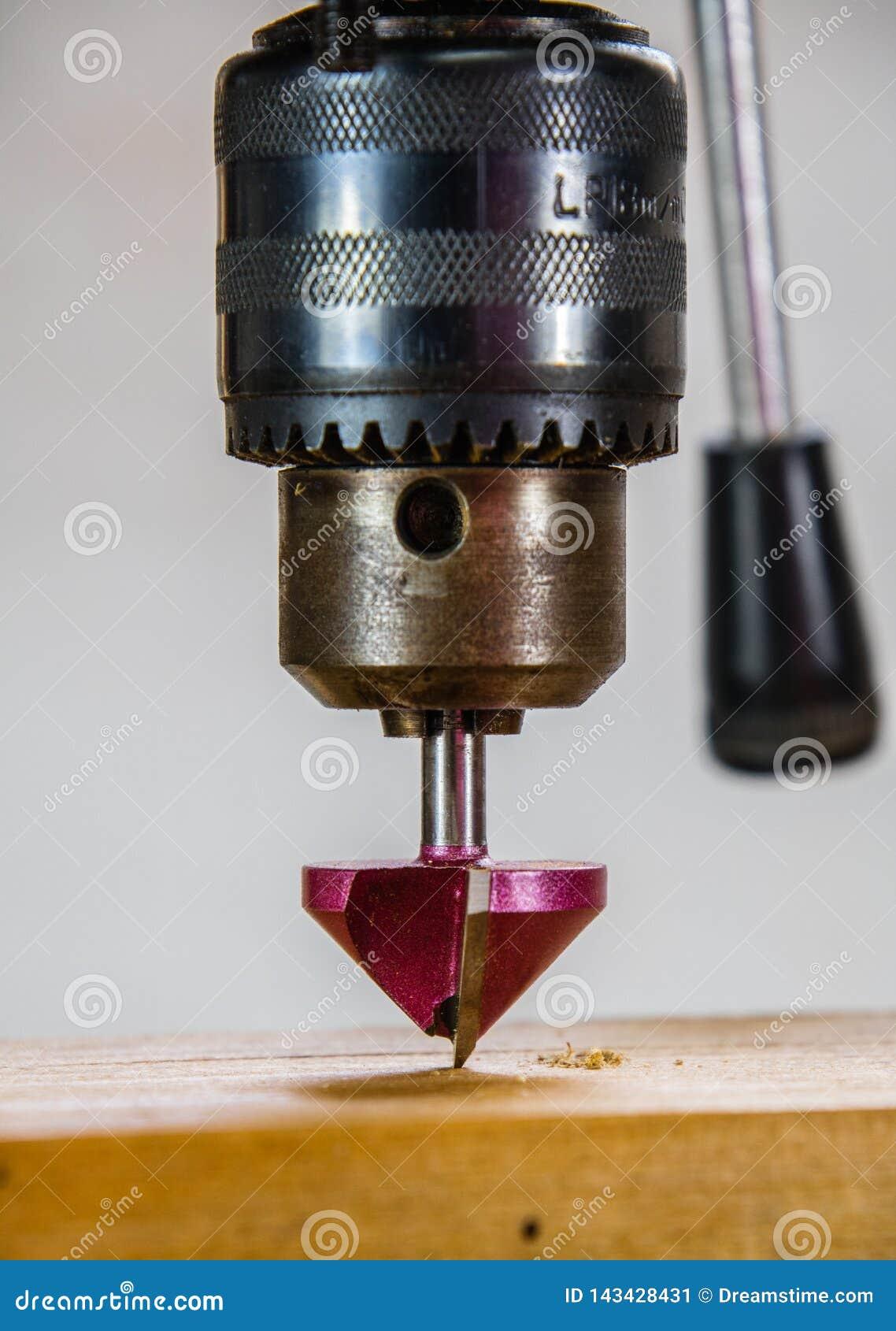Broca do eixo que fura uma madeira com broca normal