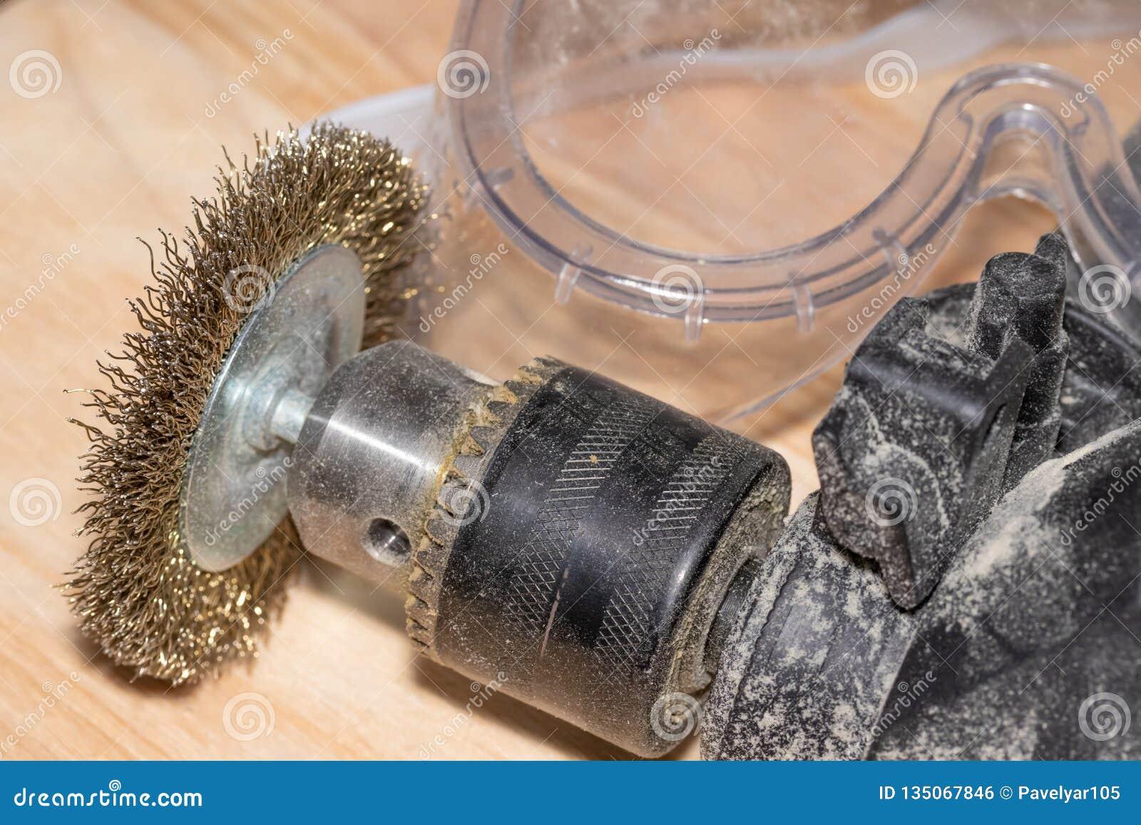 Broca elétrica com o disco para trabalhar superfícies e óculos de proteção de madeira em uma tabela de madeira da obra de carpint
