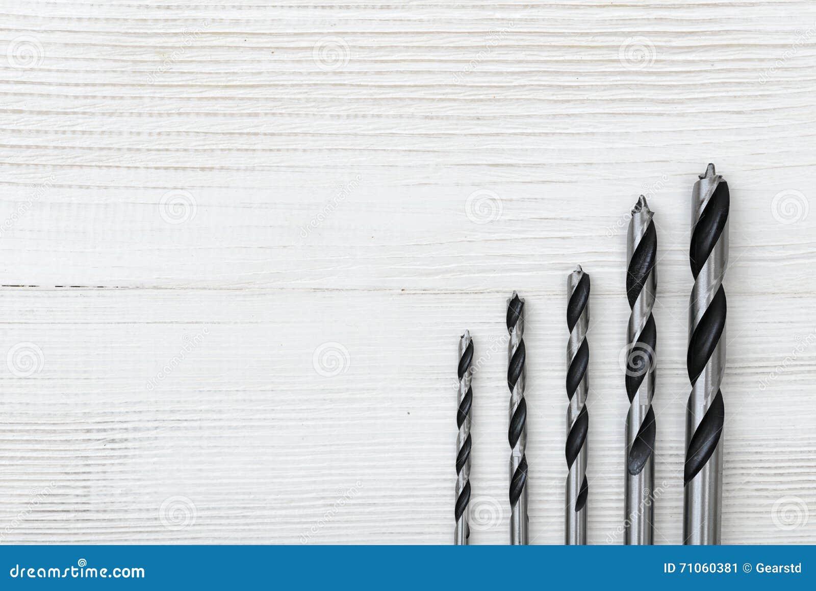 Brocas diferentes do tamanho afixadas do mais alto ao mais baixo em uma superfície de madeira