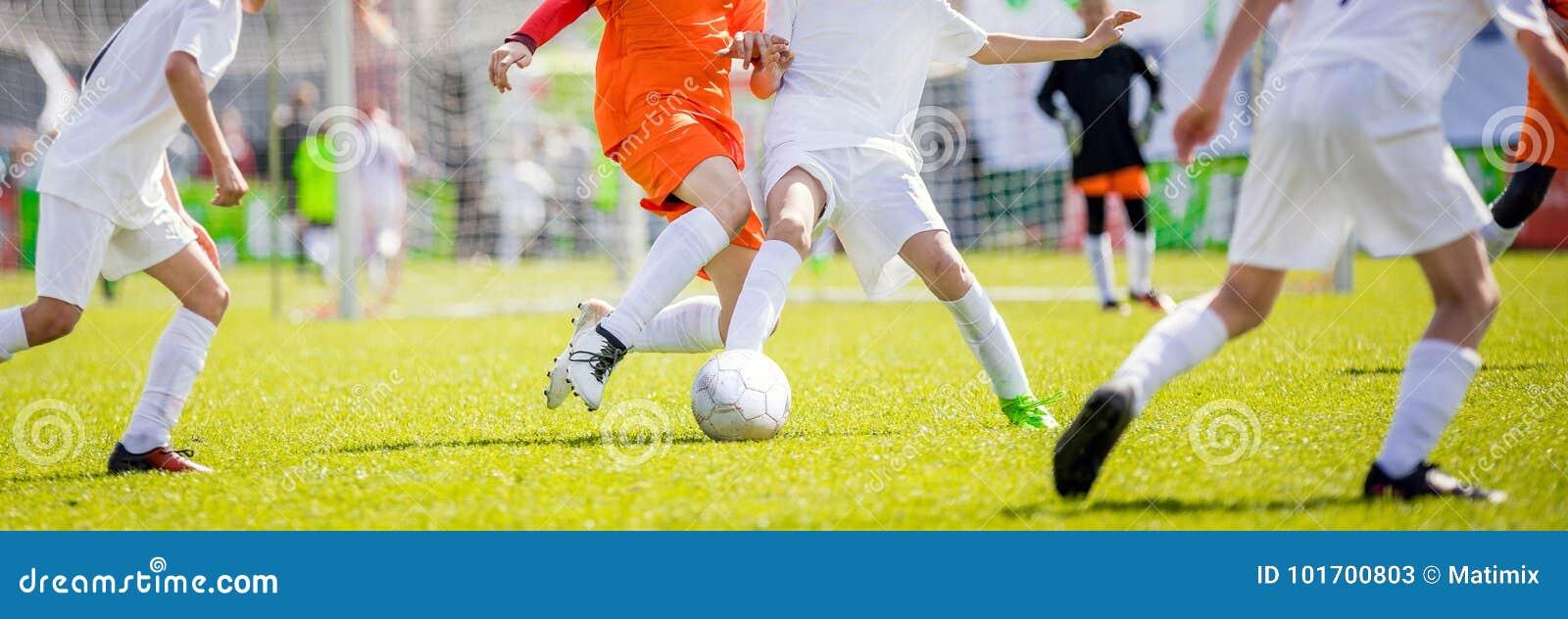 Brocas do futebol do ` s das crianças Crianças que retrocedem o fósforo de futebol no passo