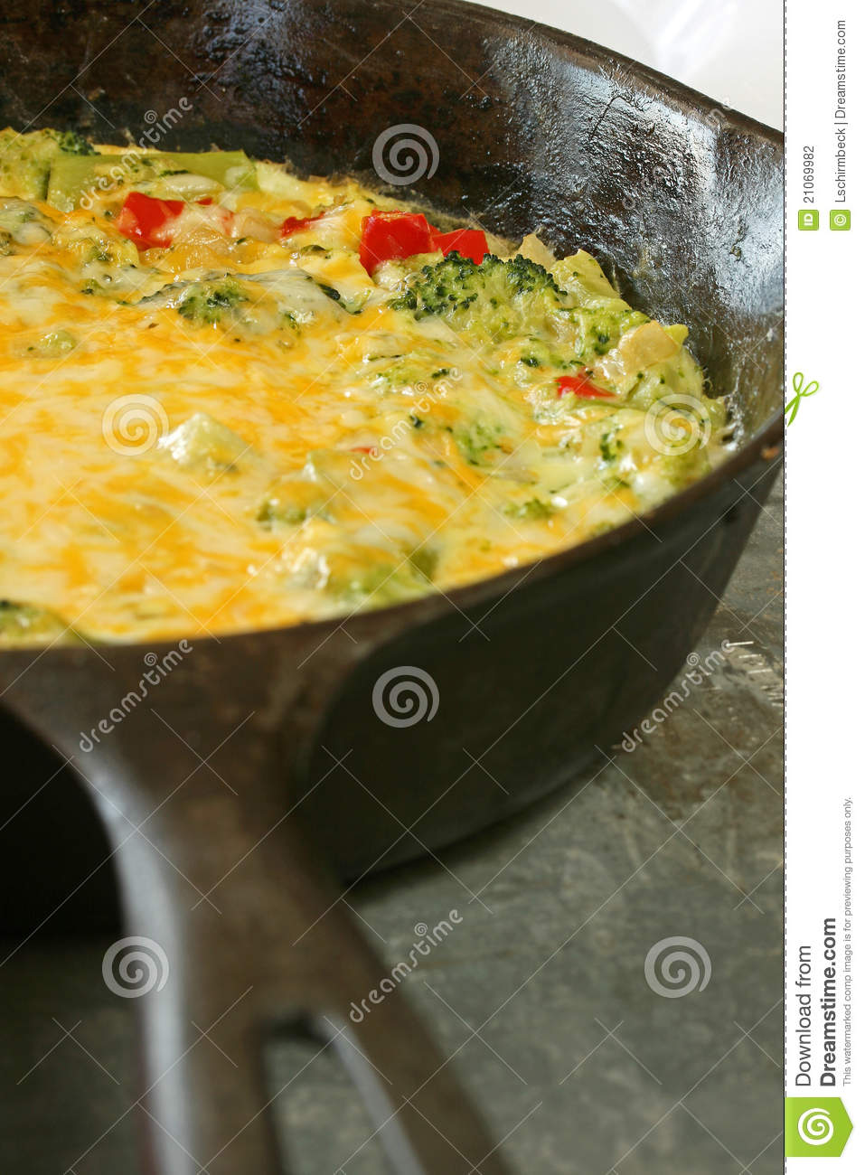 Skillet of broccoli cheese frittata with red peppers and cheese.