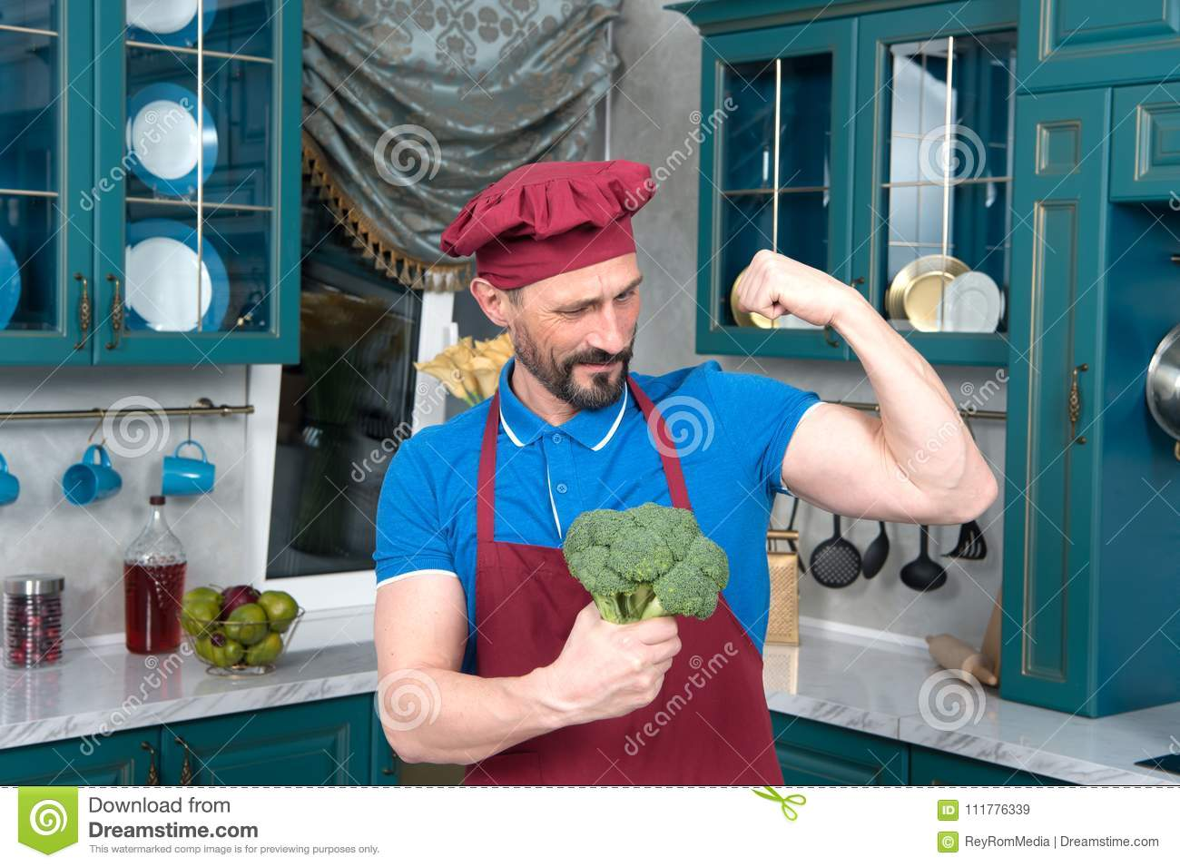 Broccoli gives power to man. bicep or broccoli chose. Guy holds broccoli in hands and shows his bicep.