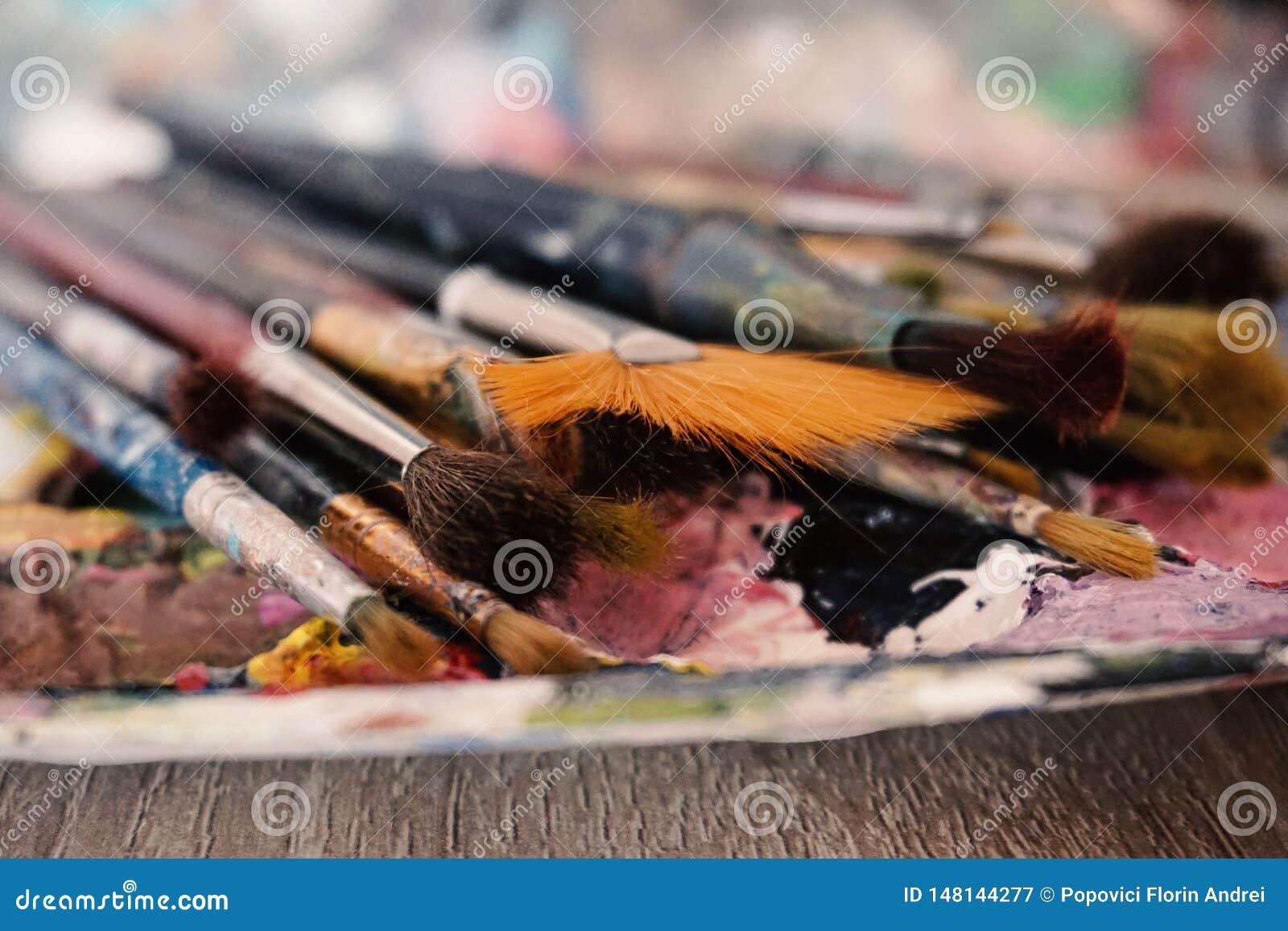 Brochas colocadas en la paleta de colores, tiro macro con el fondo borroso