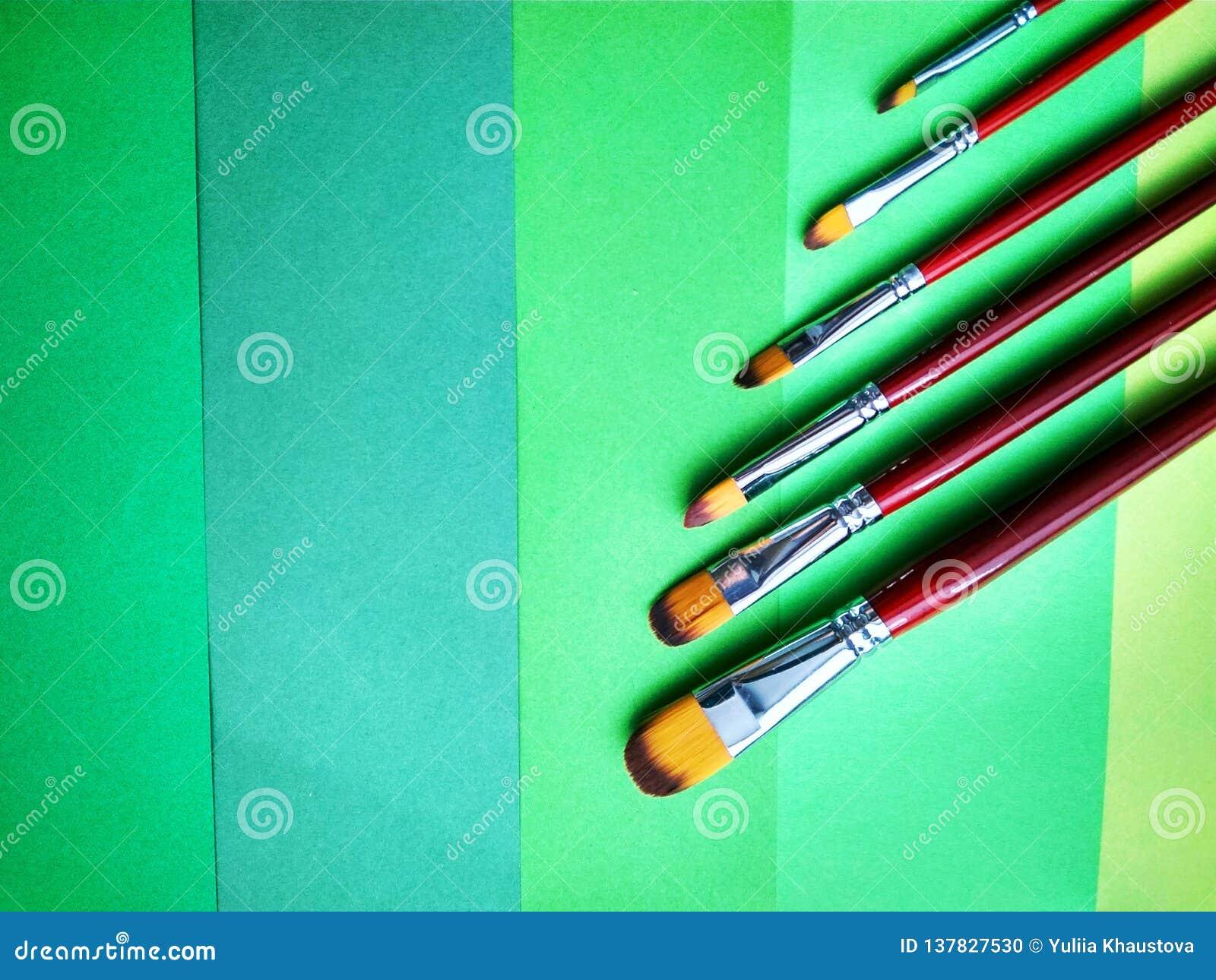 Brochas en un fondo del papel coloreado