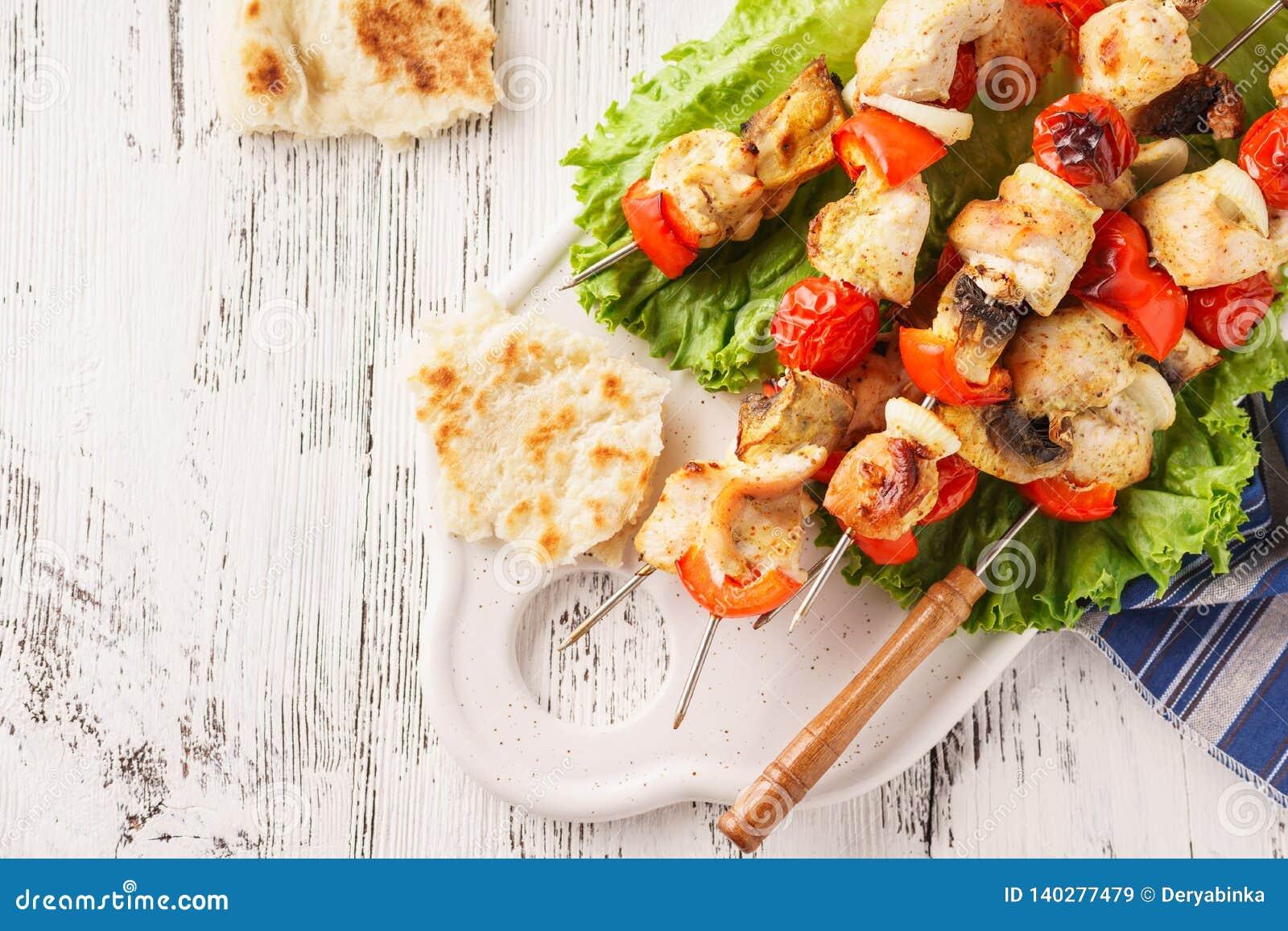 Brochettes de poulet avec des champignons, des légumes et la laitue fraîche