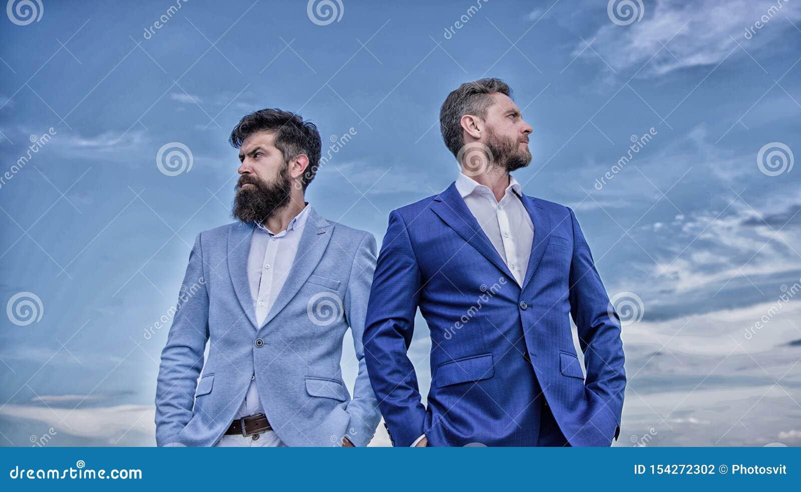 Brodaci ludzie biznesu pozuje pewnie Doskonali? w ka?dy szczeg?le Biznesowych m??czyzn niebieskiego nieba statywowy t?o Biznes
