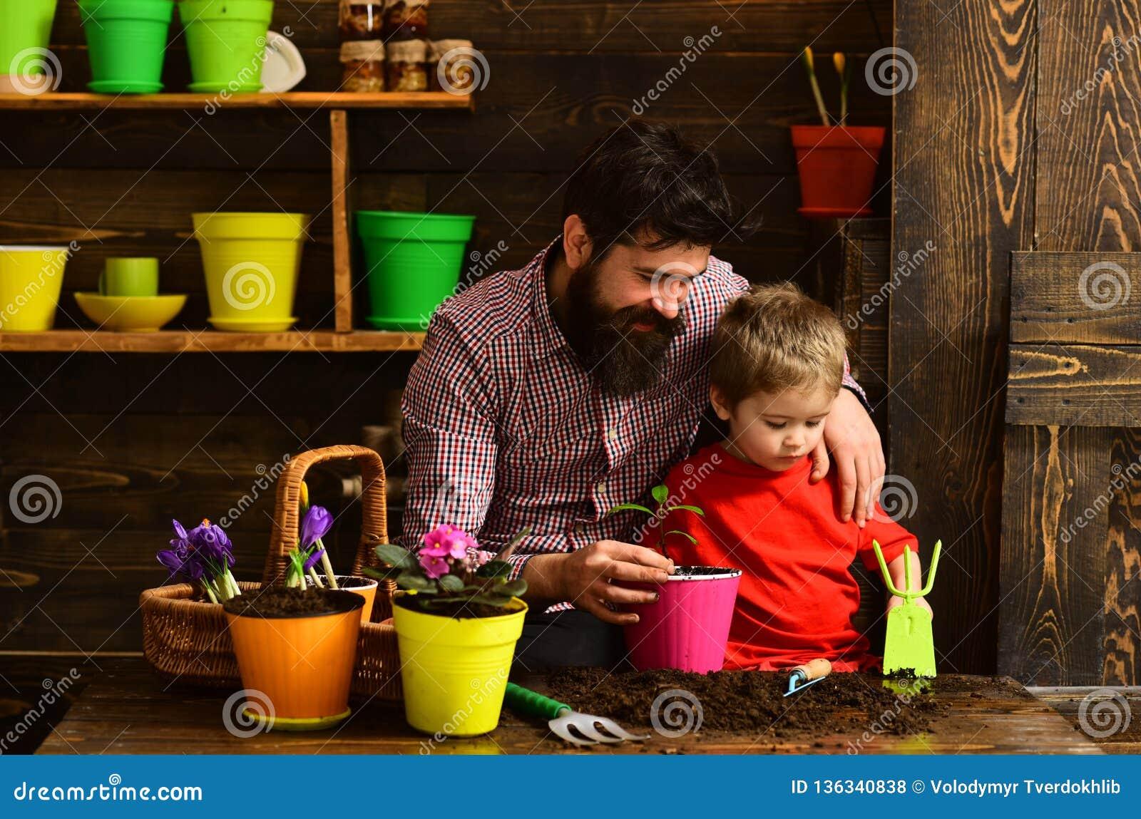 Brodata mężczyzny i chłopiec dziecka miłości natura szczęśliwe ogrodniczki z wiosna kwiatami Rodzinny dzień charcica Ojciec i