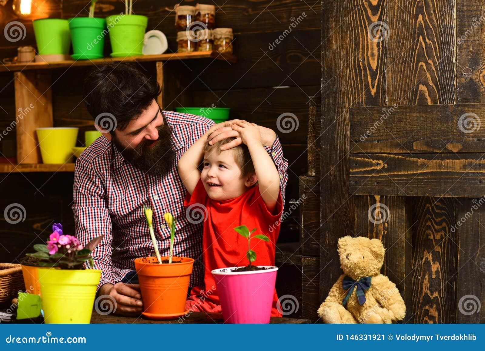 Brodata m??czyzny i ch?opiec dziecka mi?o?ci natura Rodzinny dzie? charcica szcz??liwe ogrodniczki z wiosna kwiatami Kwiat opieka