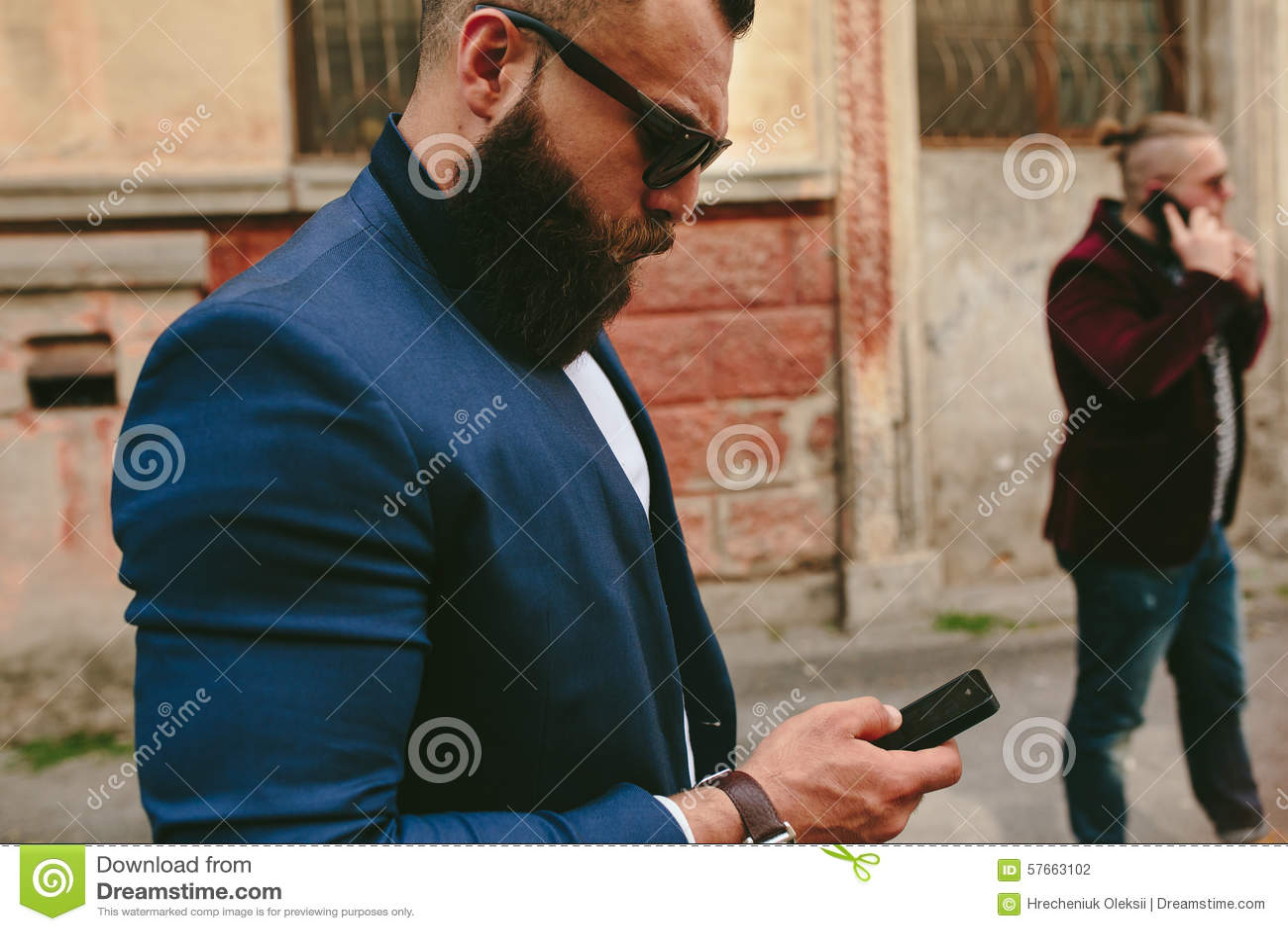 Brodaty biznesmen patrzeje telefon