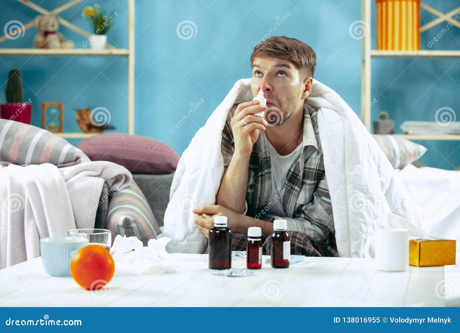 Brodaty chory mężczyzna z płomienicy obsiadaniem na kanapie w domu Choroba, grypa, bólowy pojęcie domowy relaks Opieka zdrowotna