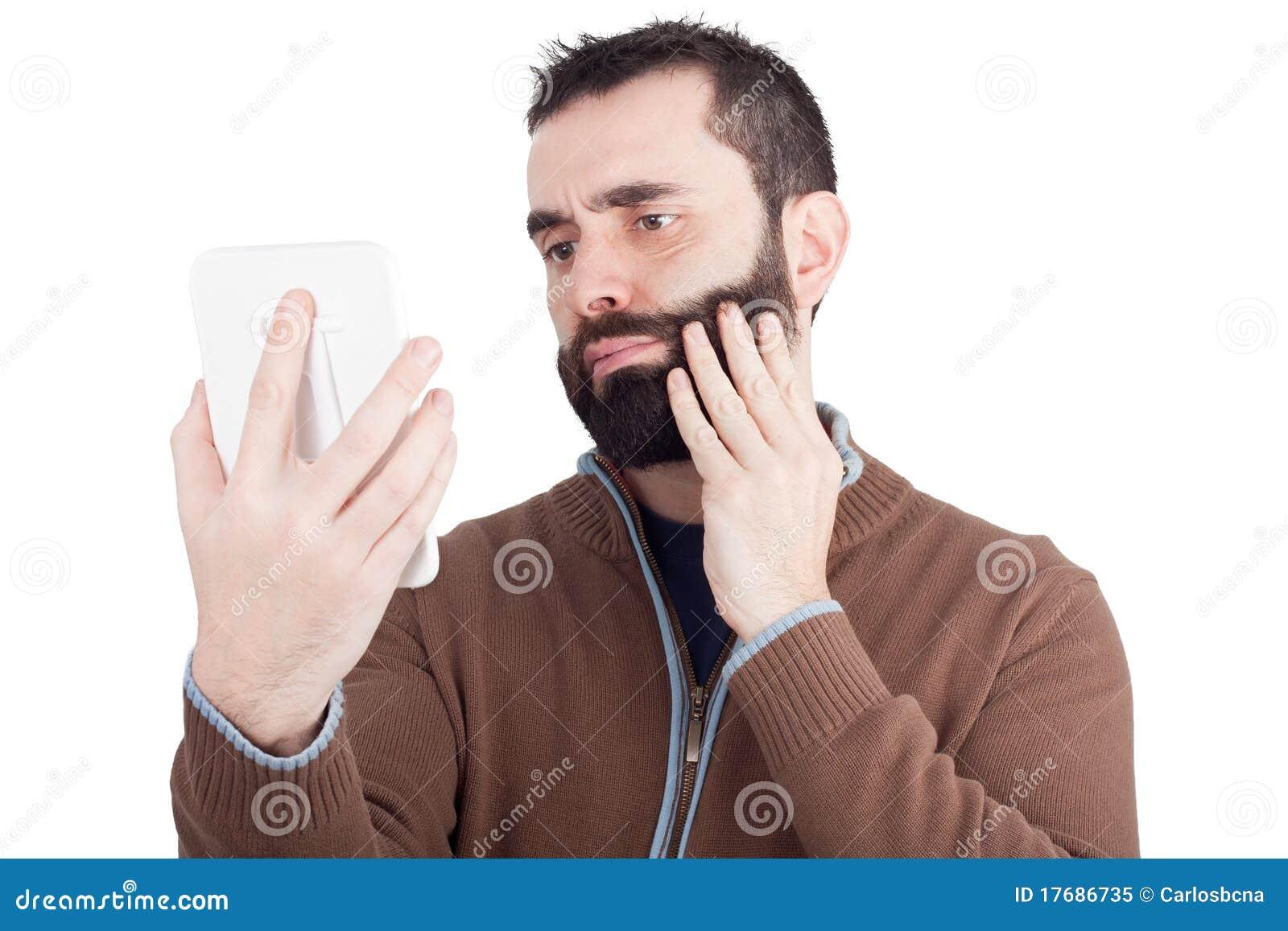 Brodaty lustro ręki przyglądający mężczyzna lustro