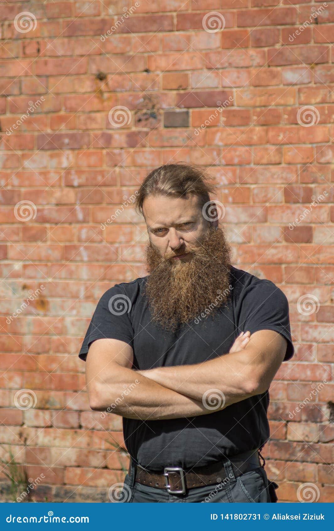 Brodaty mężczyzna na czerwonym ściany z cegieł tle