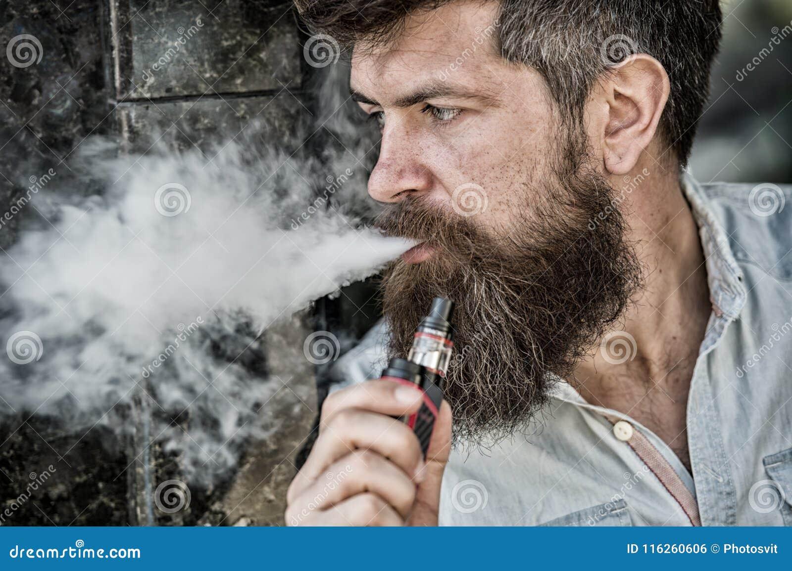 Brodaty mężczyzna dymi vape, białe chmury dymu Elektroniczny Papierosowy pojęcie Mężczyzna z długą brodą patrzeje zrelaksowanym c