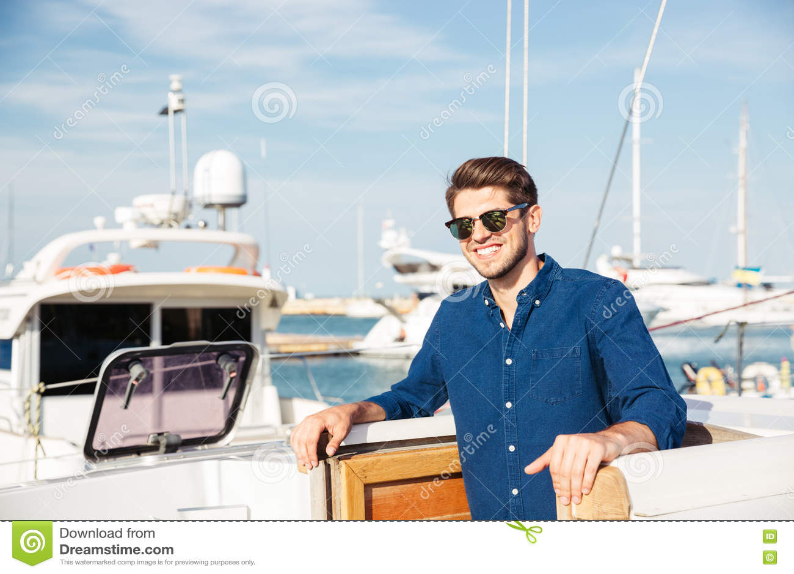 Brodaty mężczyzna jest ubranym okulary przeciwsłonecznych i pozycję na jachcie