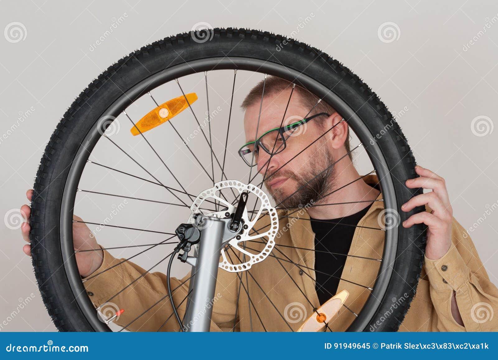 Brodaty mężczyzna sprawdza uczepienie frontowy koło